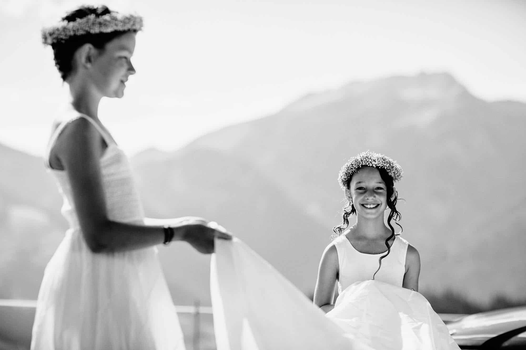 Blumenmädchen hilft das Brautkleid tragen und lacht