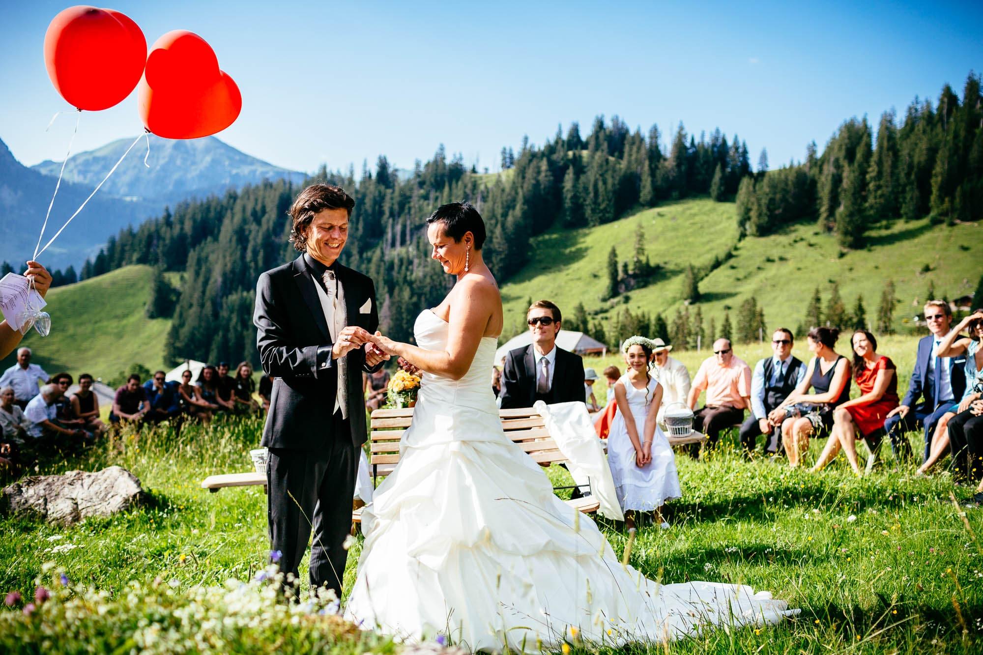 Brautpaar steckt Ehering an auf einer Alpwiese
