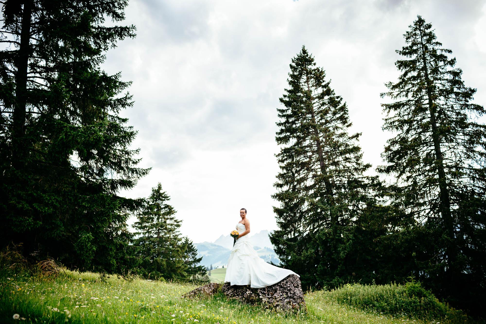 Braut steht auf einem Fels inmitten Alpwiese und hohen Tannen
