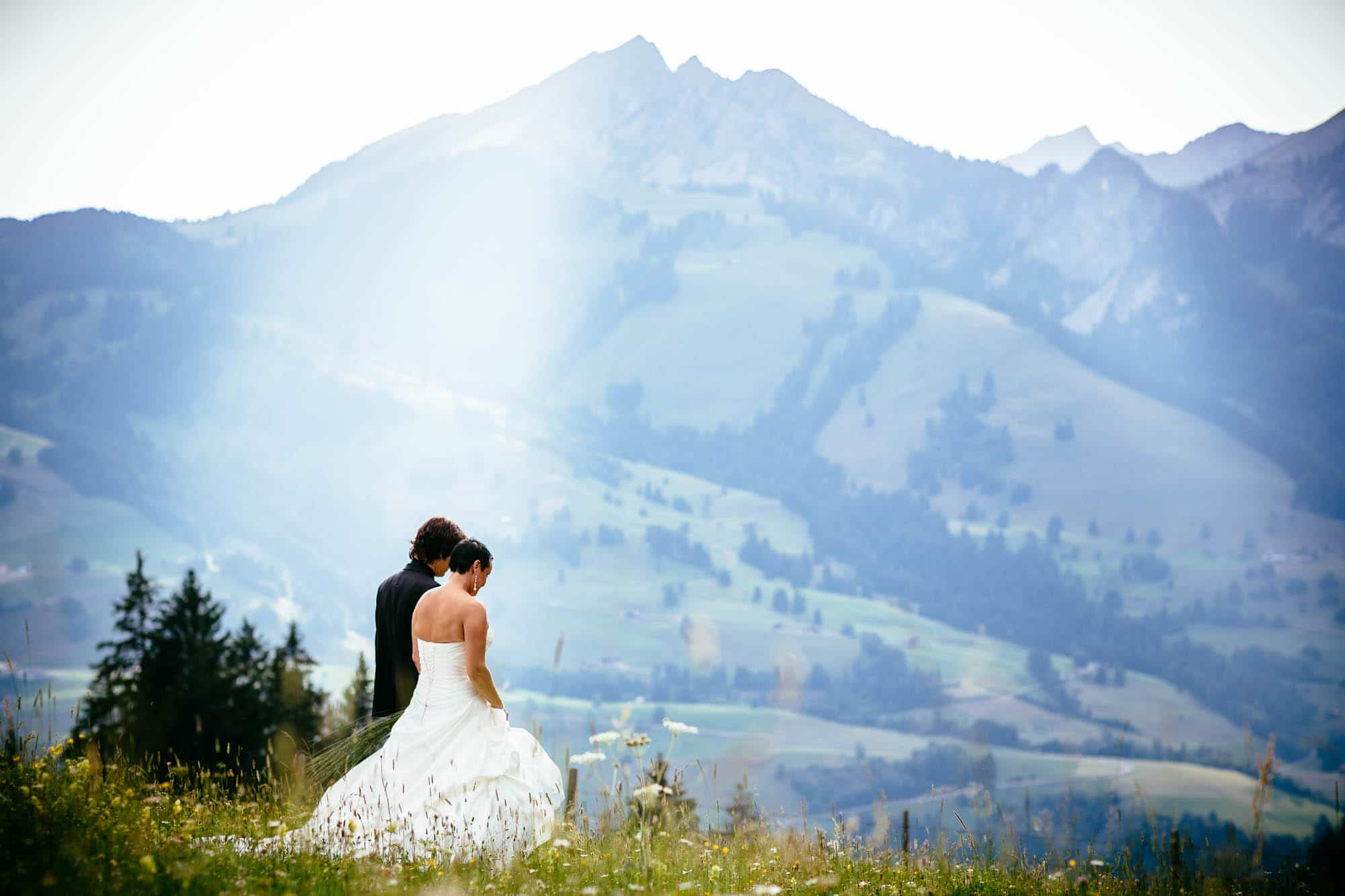 Brautpaarfotos auf einer Alpwiese mit Berg im Hintergrund