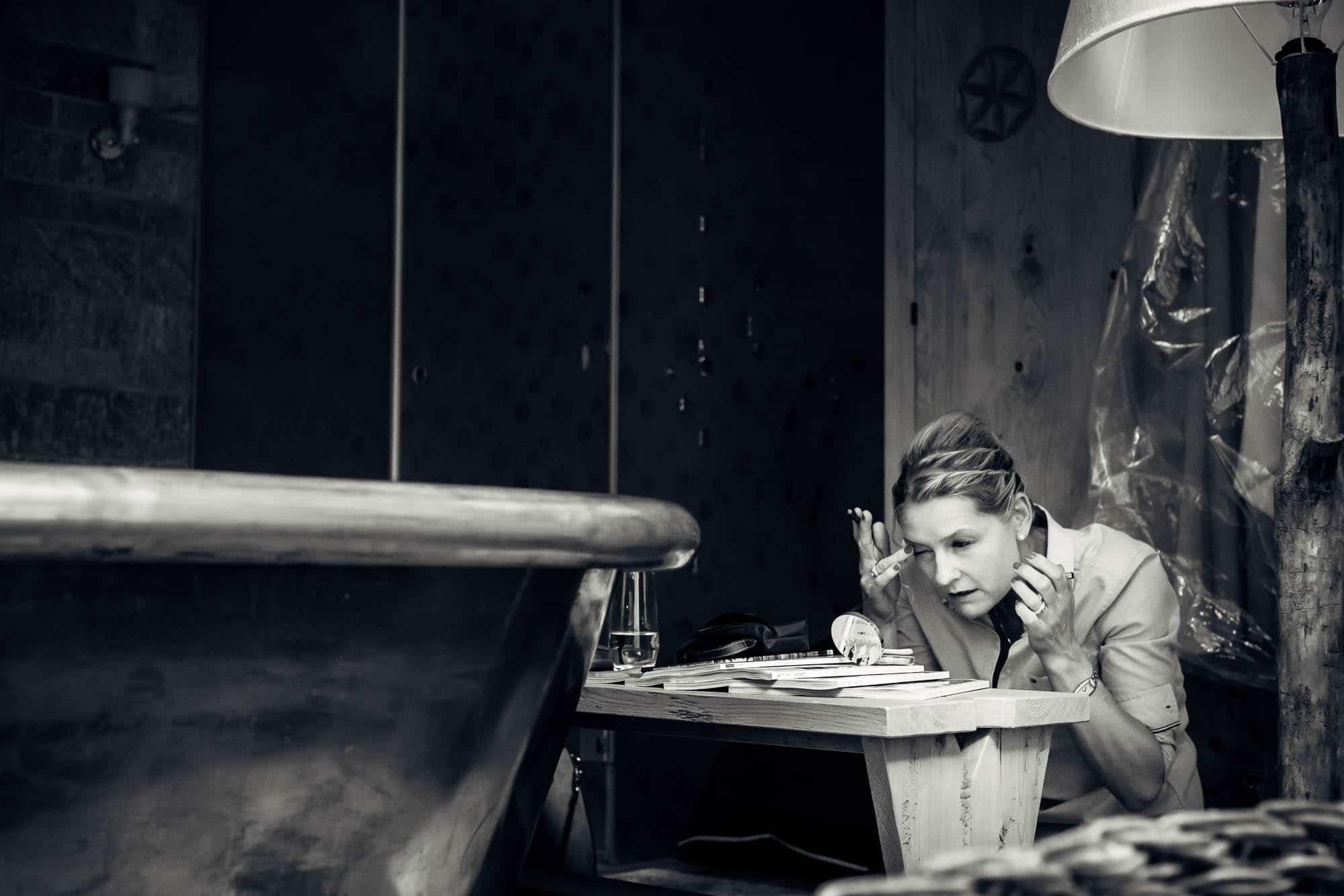 Trauzeugin schminkt sich knieend vor kleinem Taschenspiegel