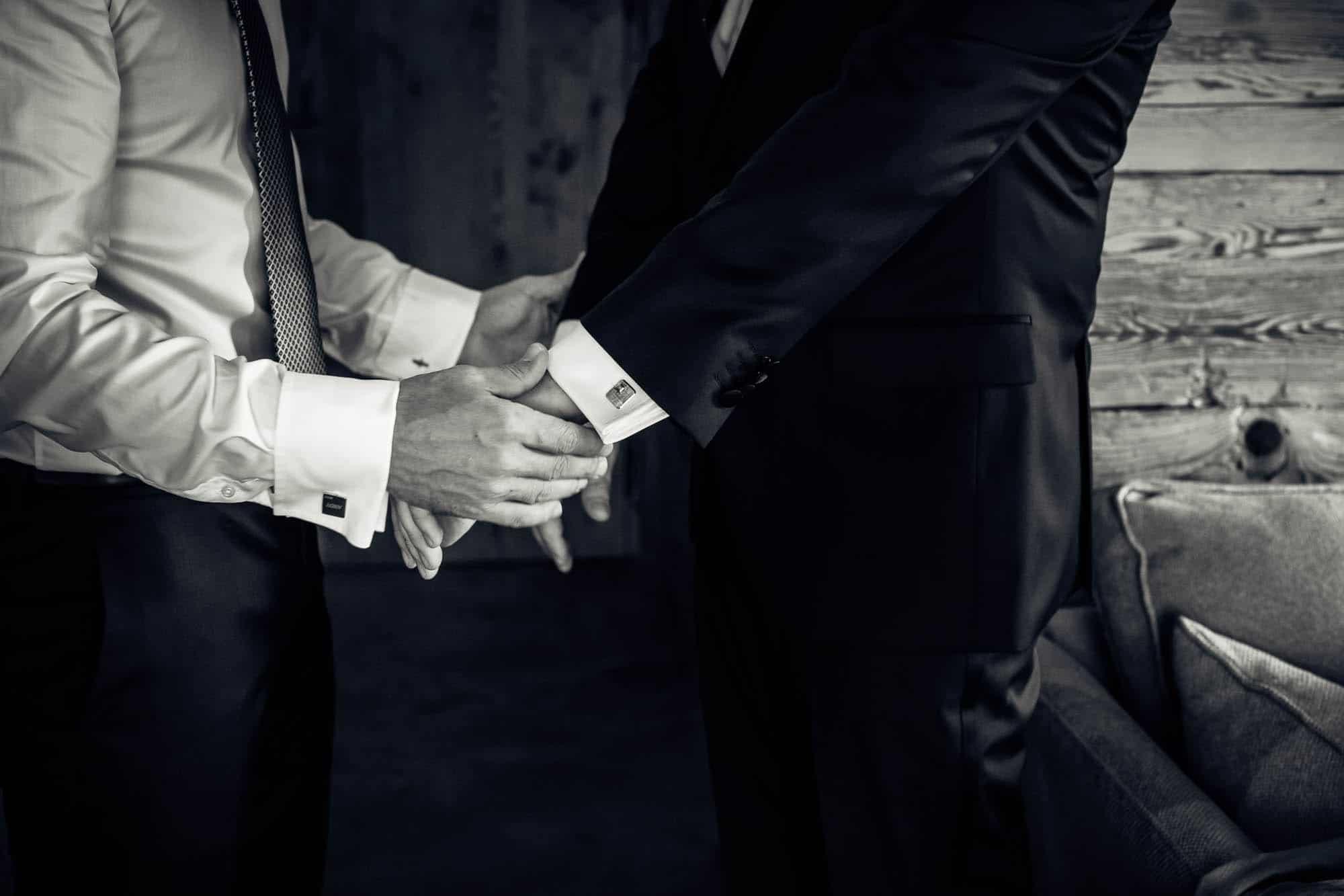 Trauzeuge hilft dem Bräutigam mit den Manschettenknöpfen