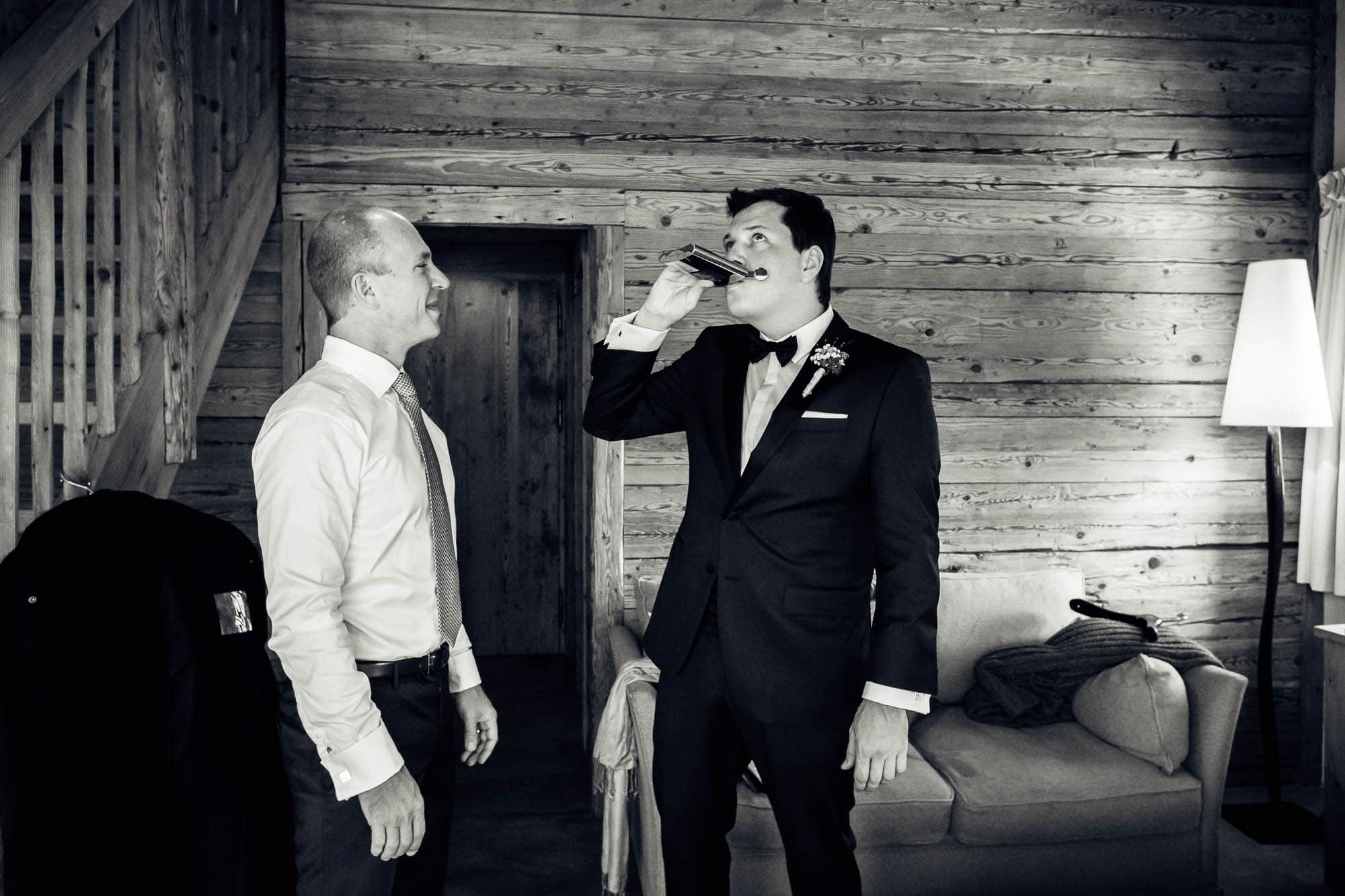 Bräutigam und Trauzeuge trinken einen Schluck aus dem Flachmann