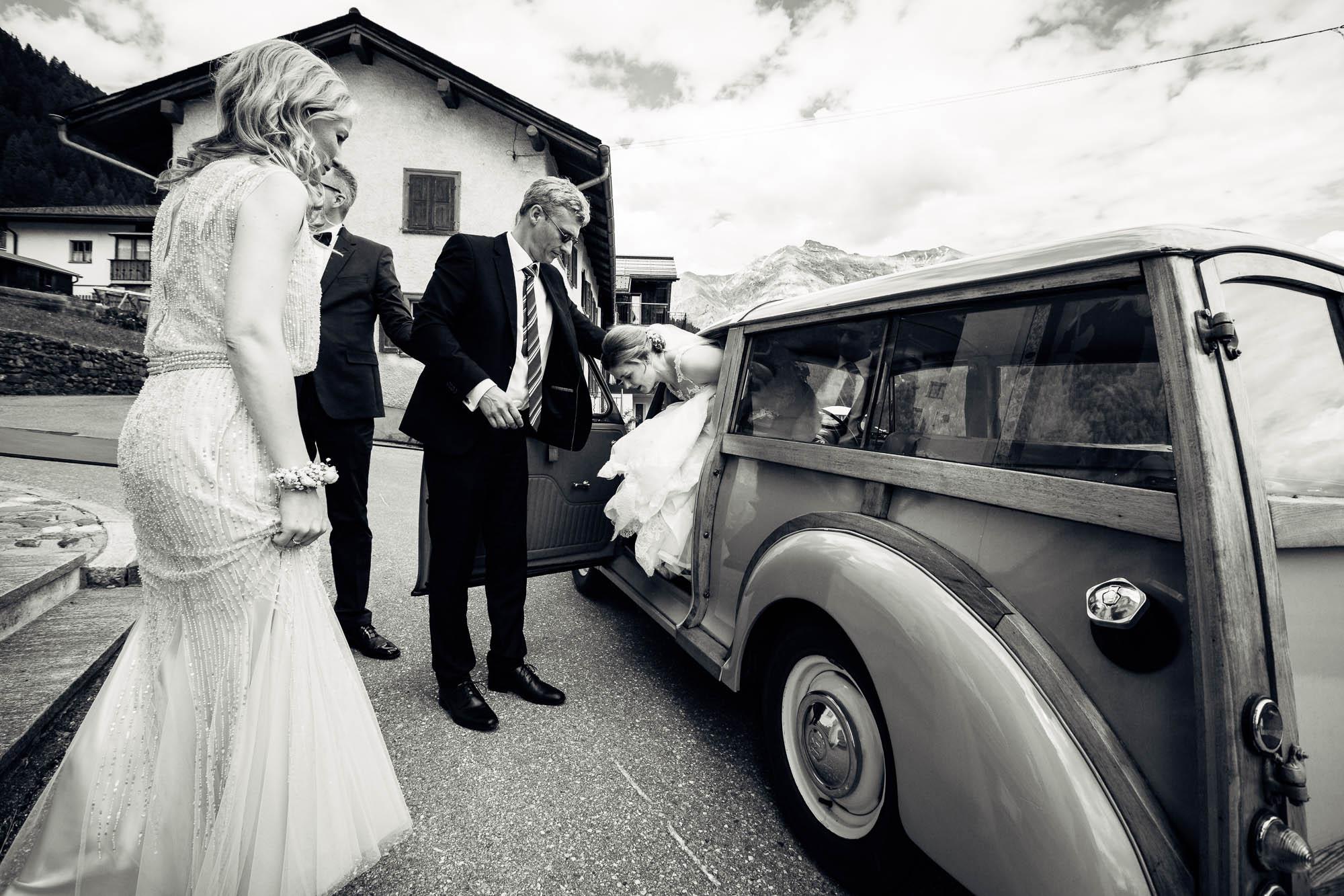 Braut steigt aus Oldtimer aus mit Hilfe vom Bruder