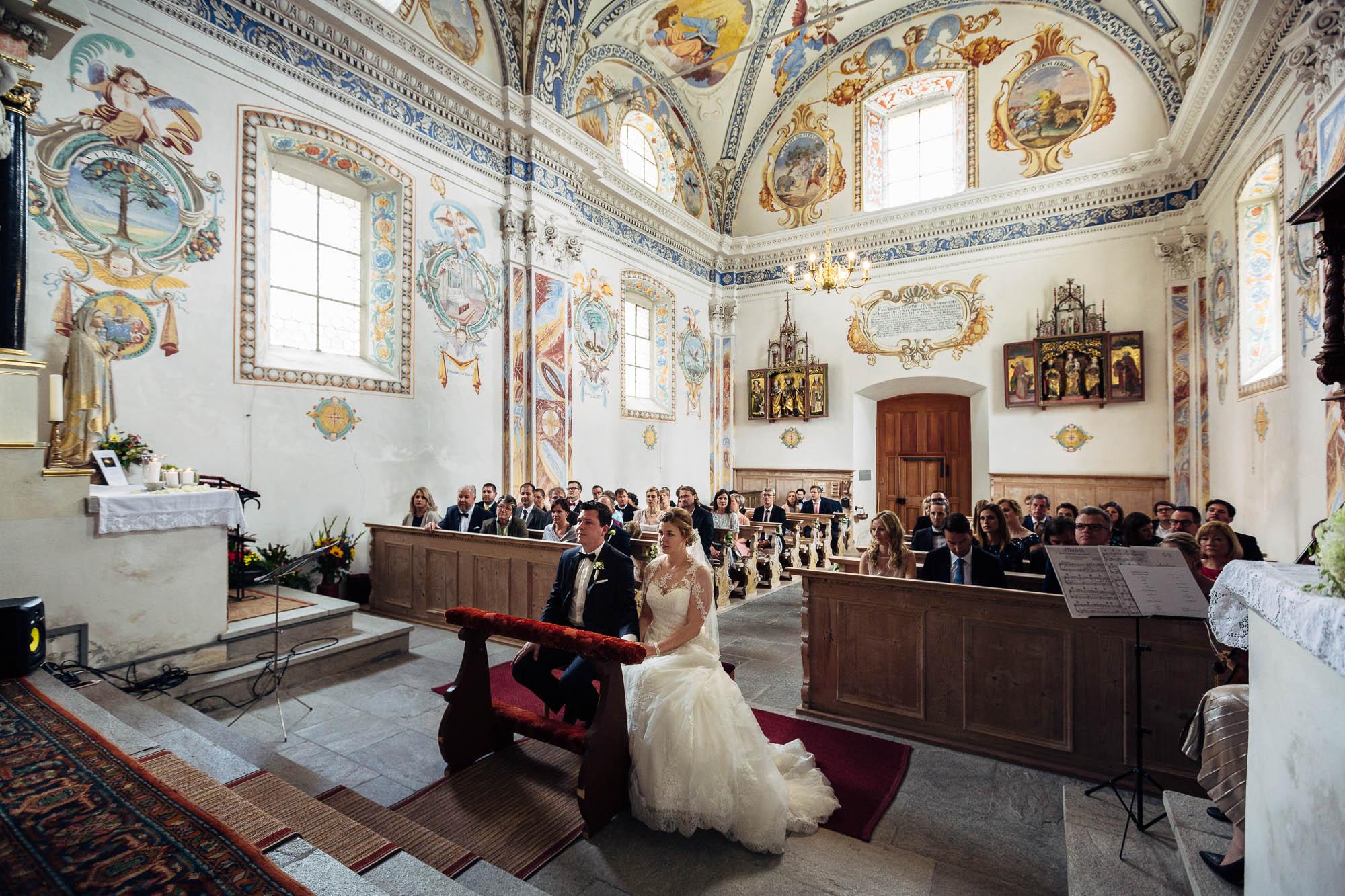 Brautpaar in der Kirche mit Hochzeitsgesellschaft