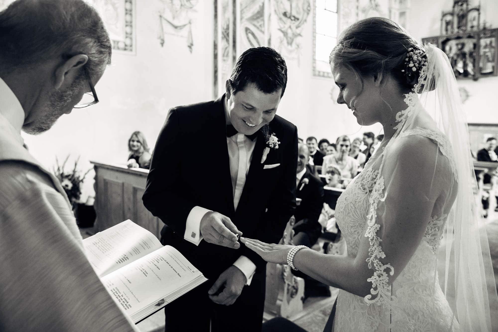 Bräutigam steckt der Braut den Ehering an