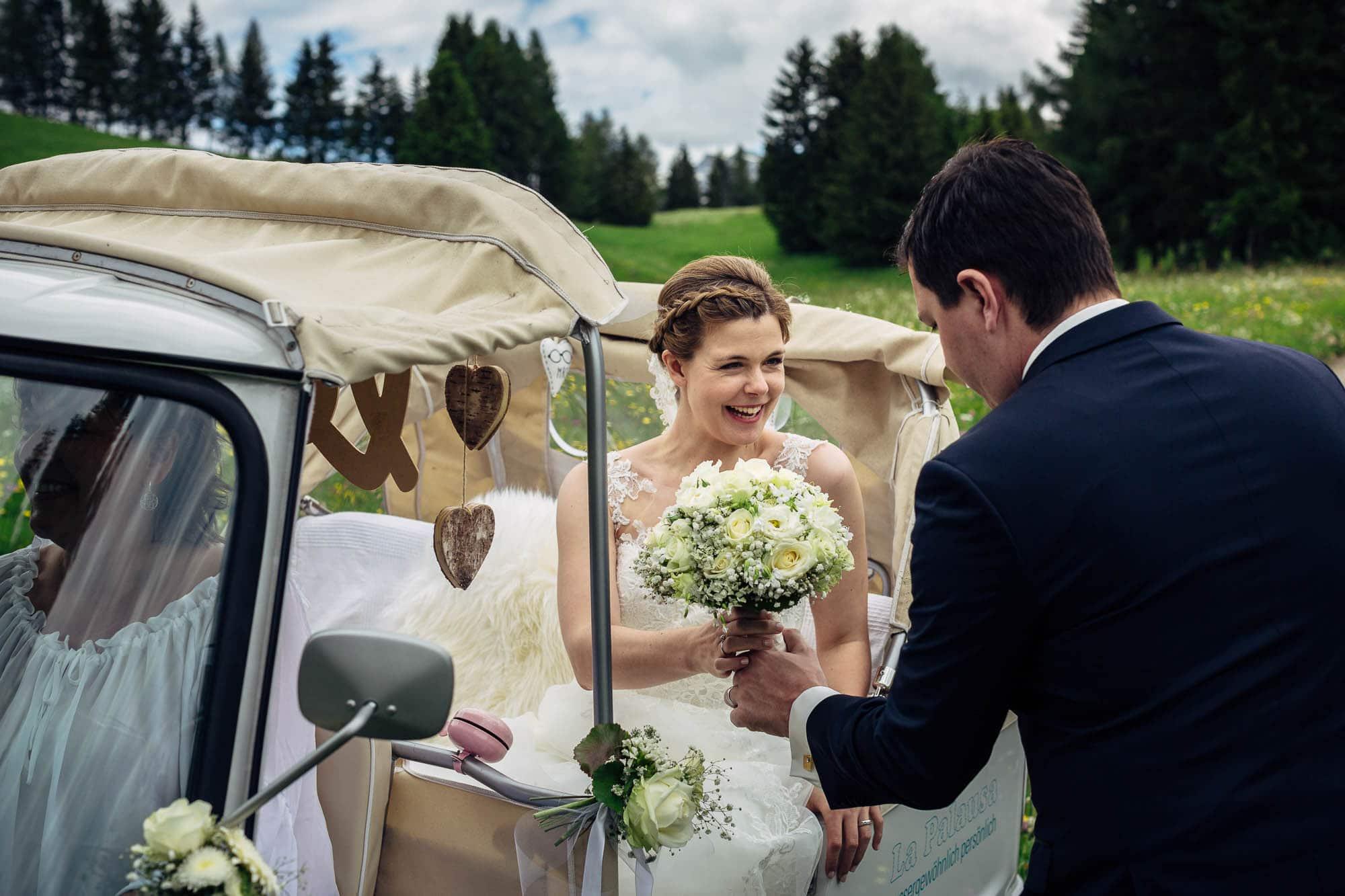 Bräutigam hilft der Braut beim Aussteigen aus Tuktuk