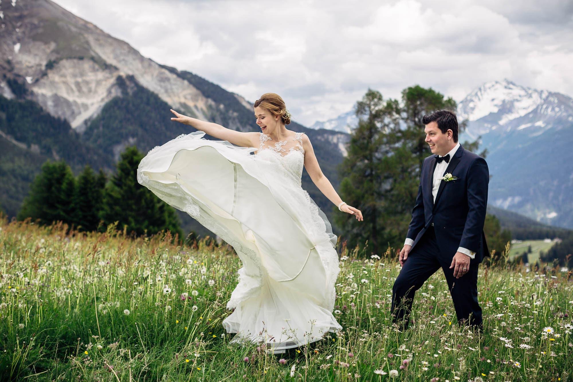 Brautkleid fliegt im Wind auf Blumenwiese beim Tanzen
