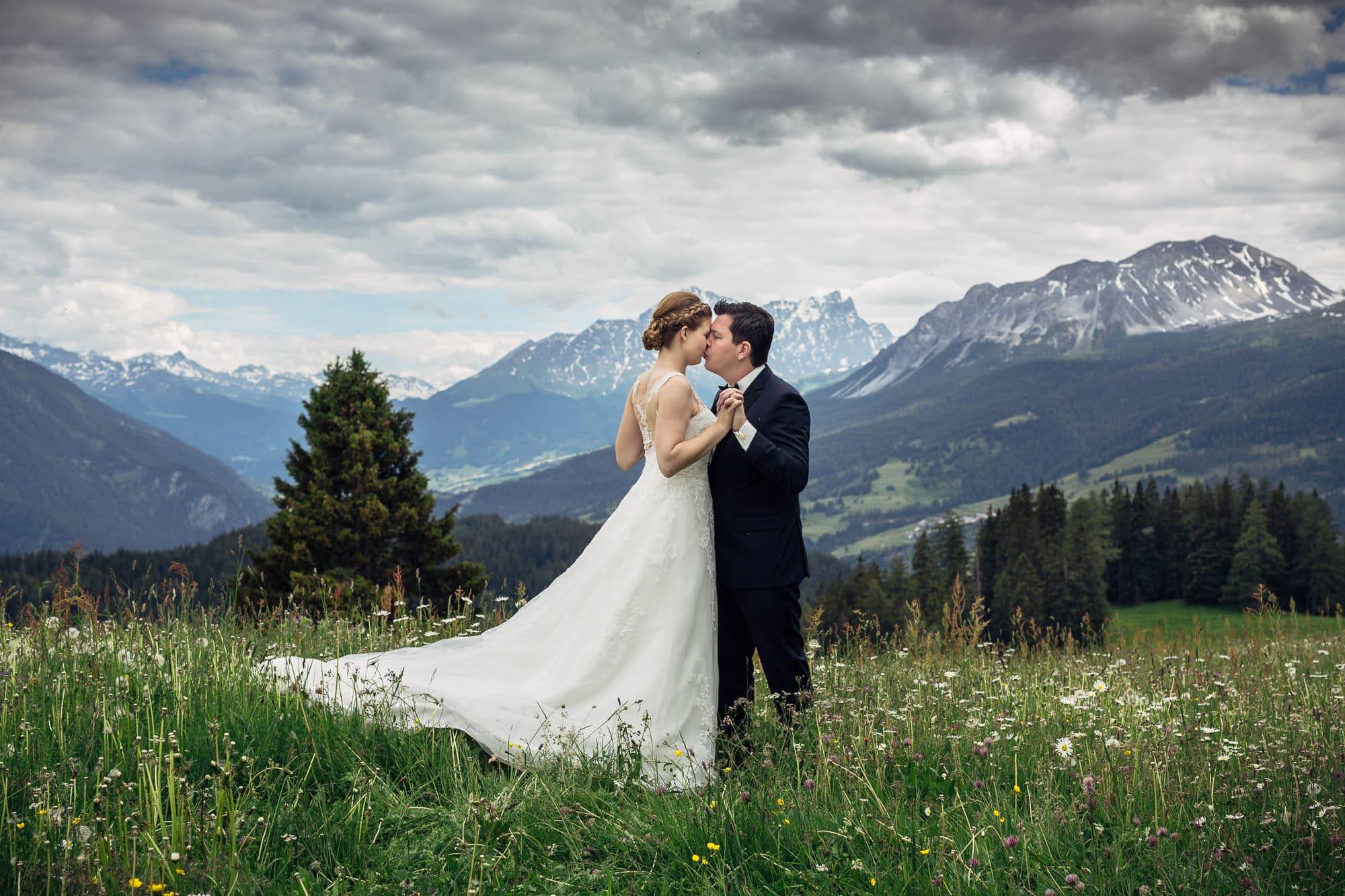 Brautpaar küsst sich auf Blumenwiese mit Berge im Hintergrund