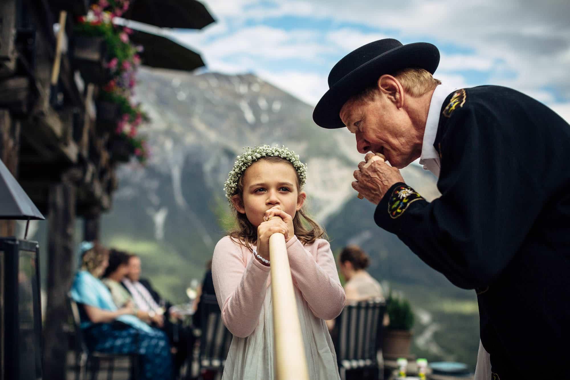 Blumenkind wird beim Alphornspielen instruiert