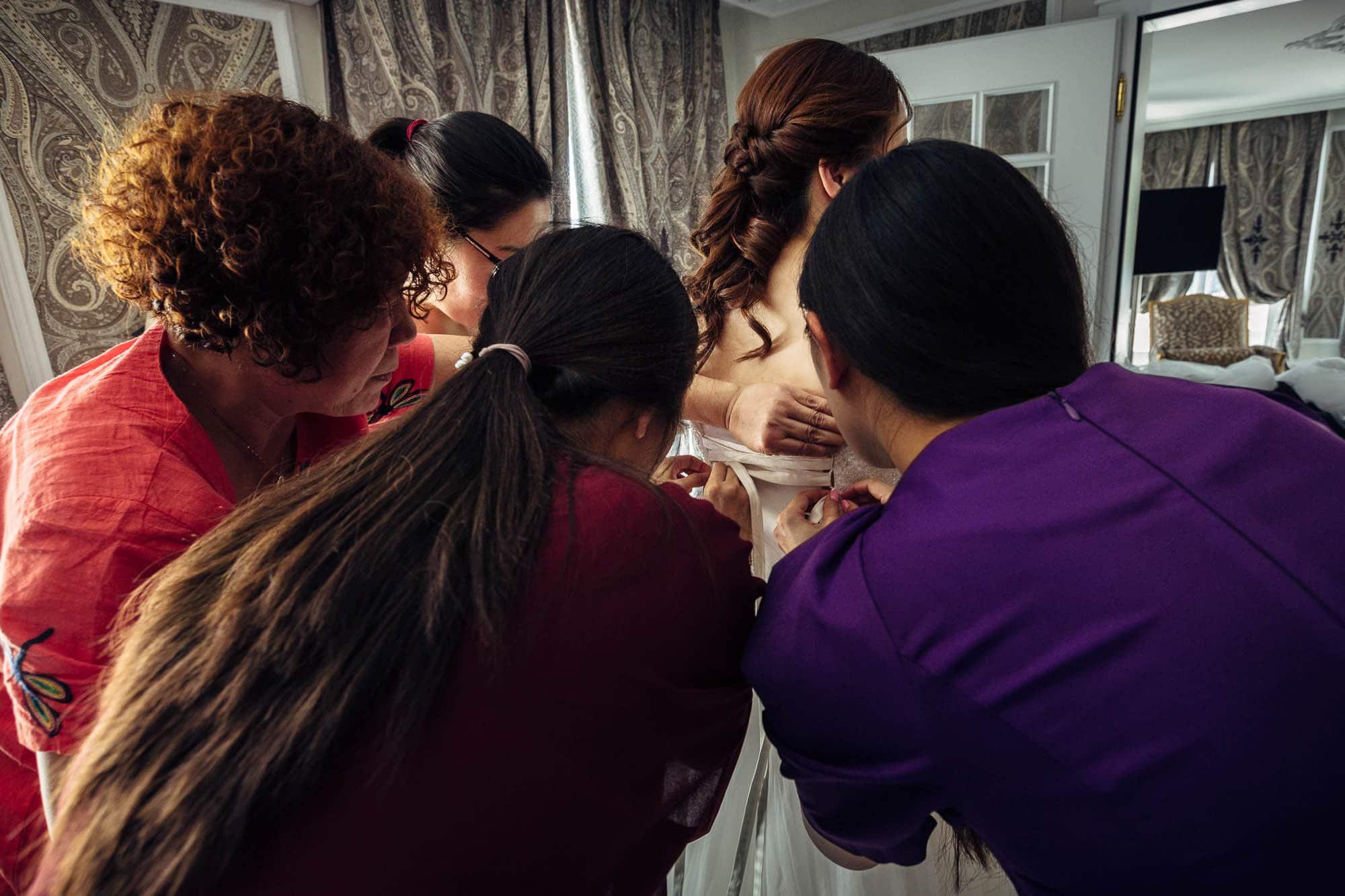 Die Braut wird von Trauzeuginnen angekleidet