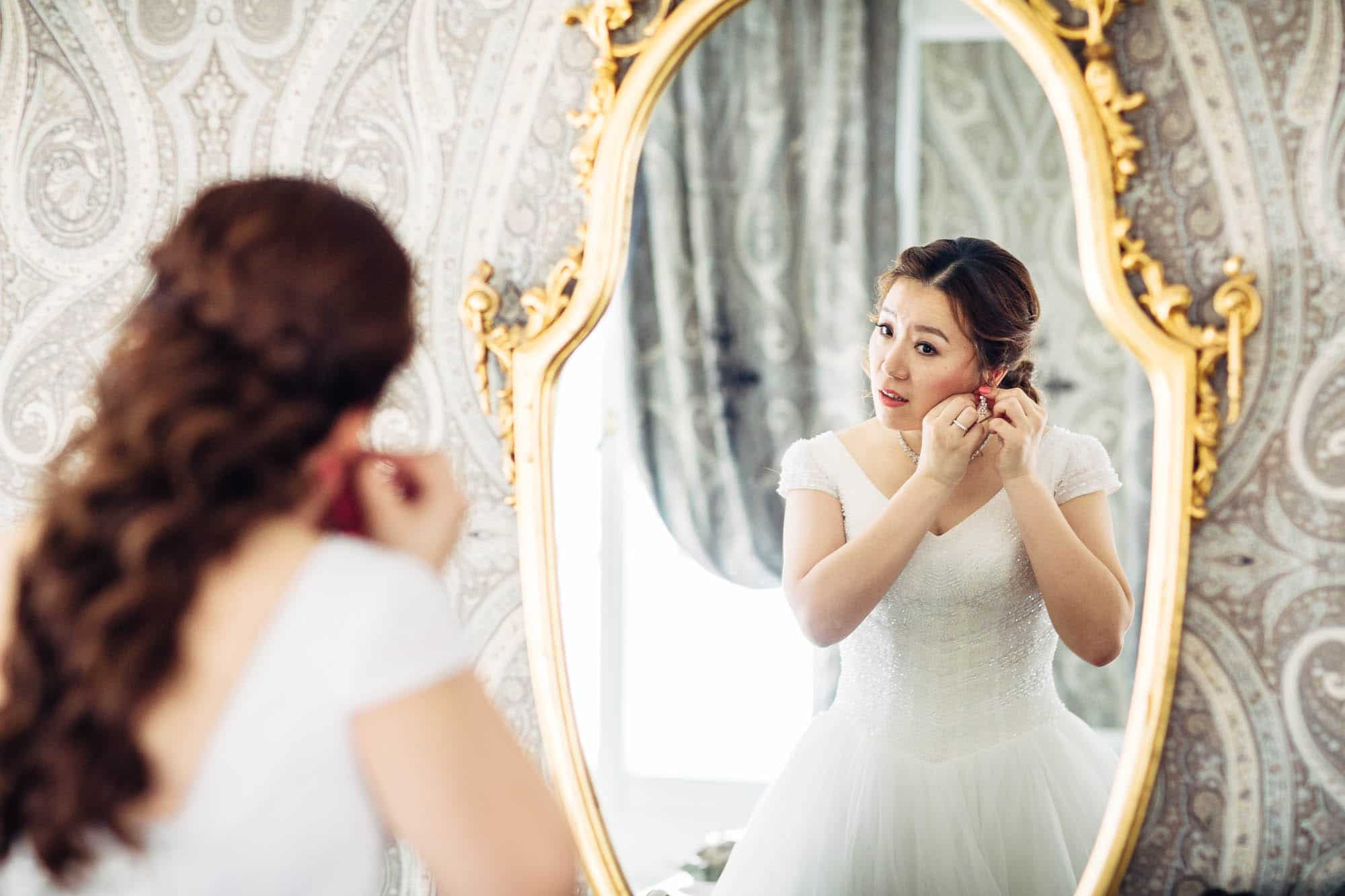 Braut steckt Ohrringe an vor dem Spiegel