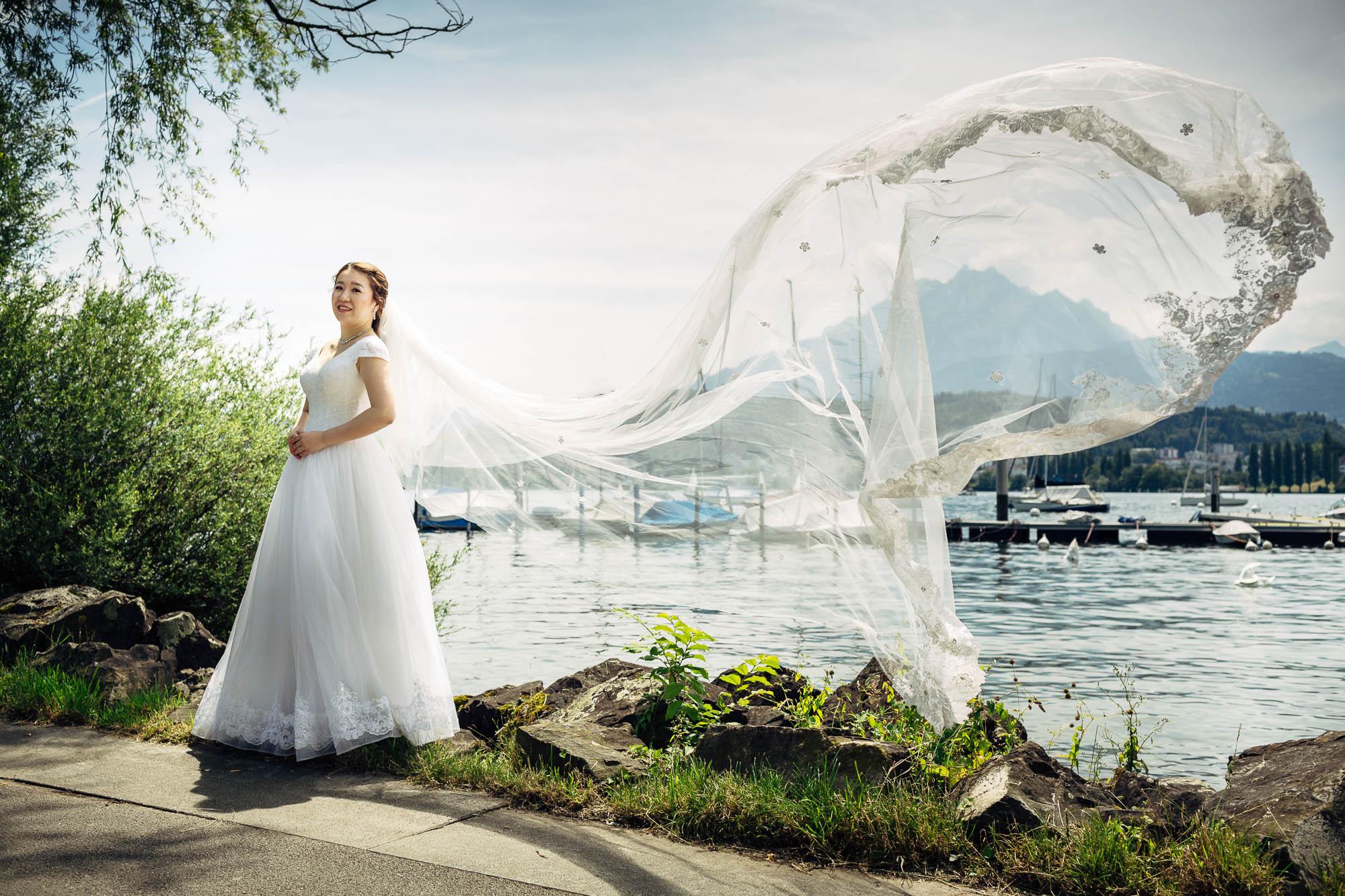 Brautschleier fliegt im Winde am See in Luzern mit Pilatus im Hintergrund
