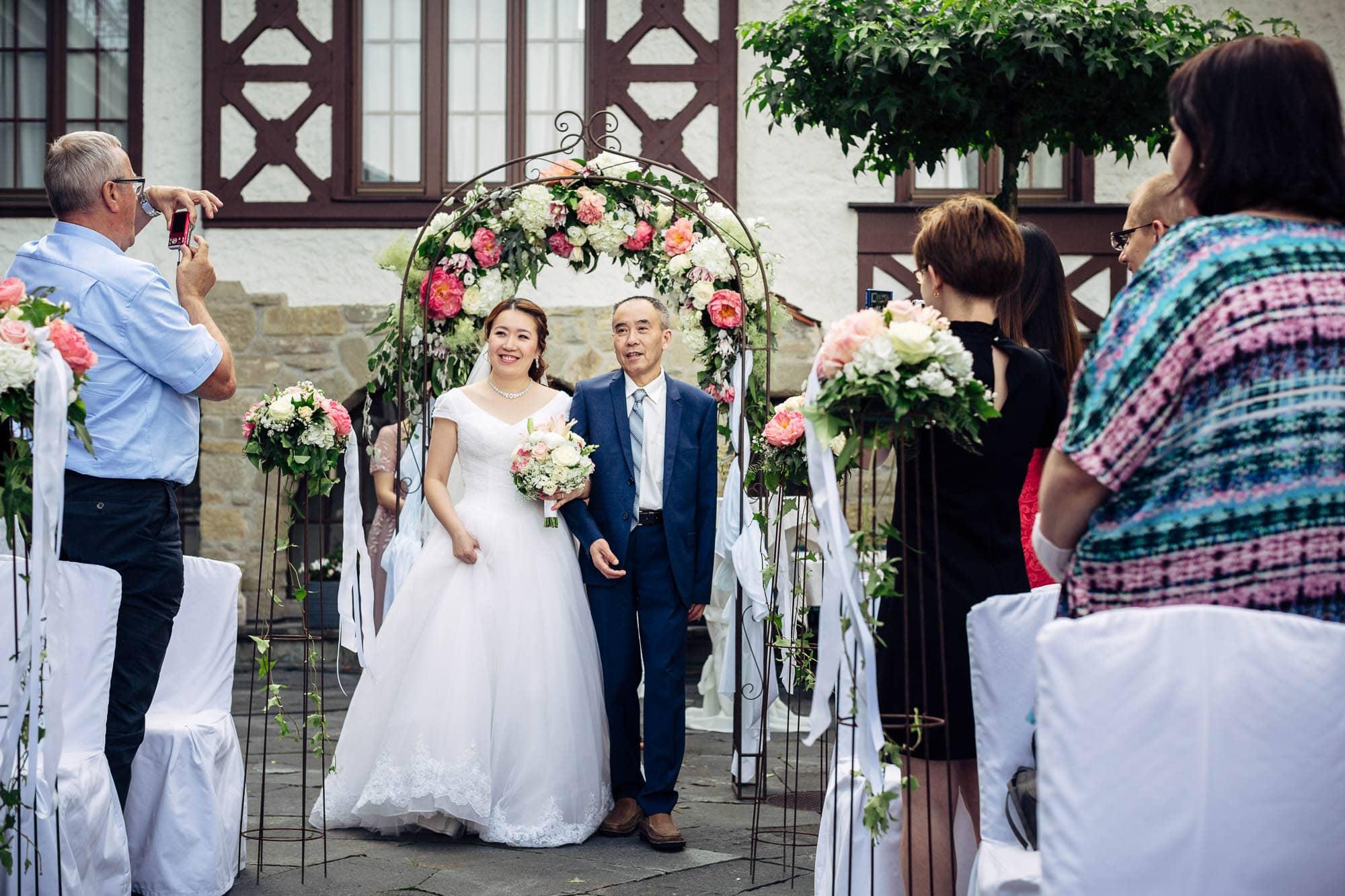 Braut wird vom Vater zur Zeremonie geleitet