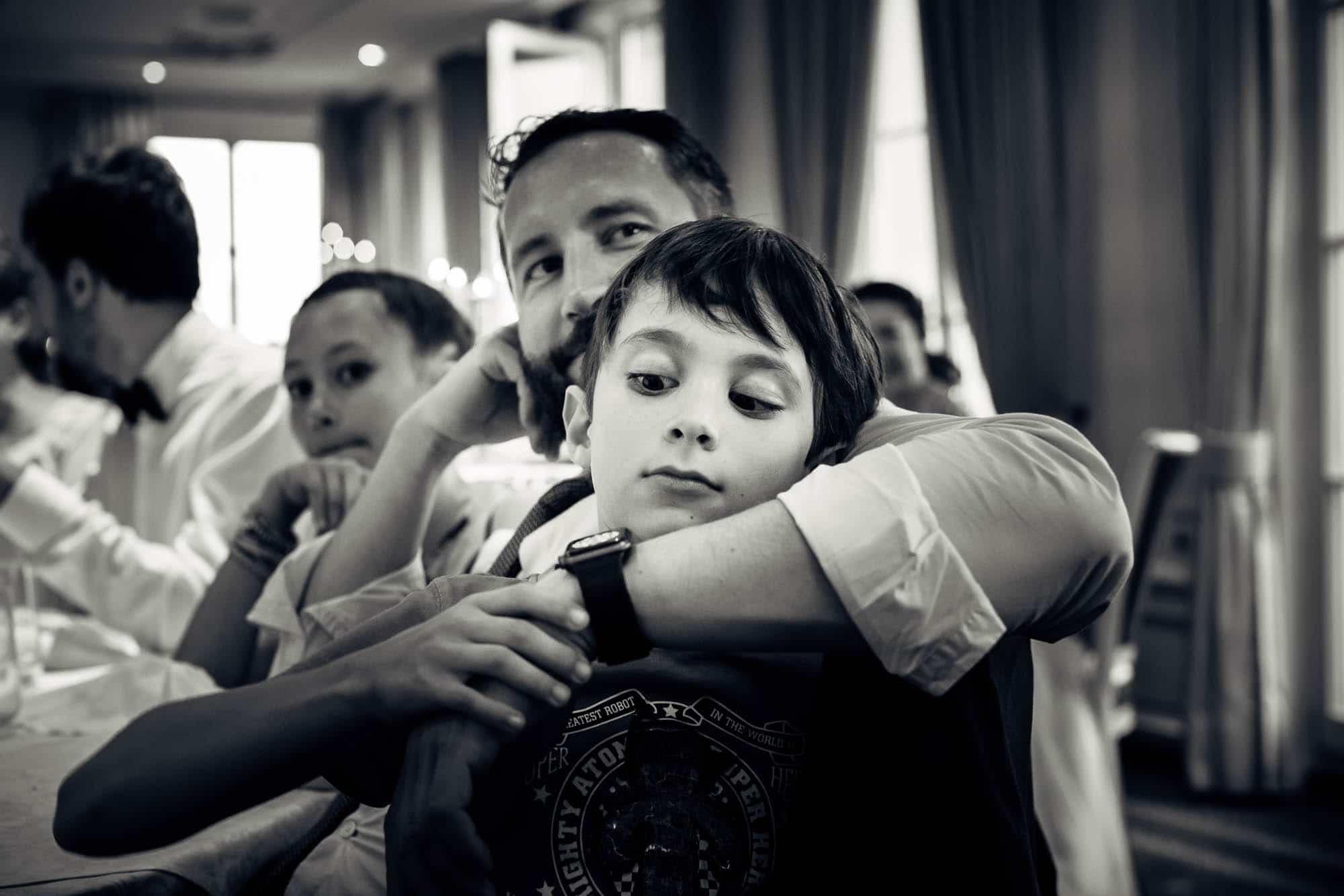 Junger schaut auf die Uhr vom Papa wenn's endlich fertig ist