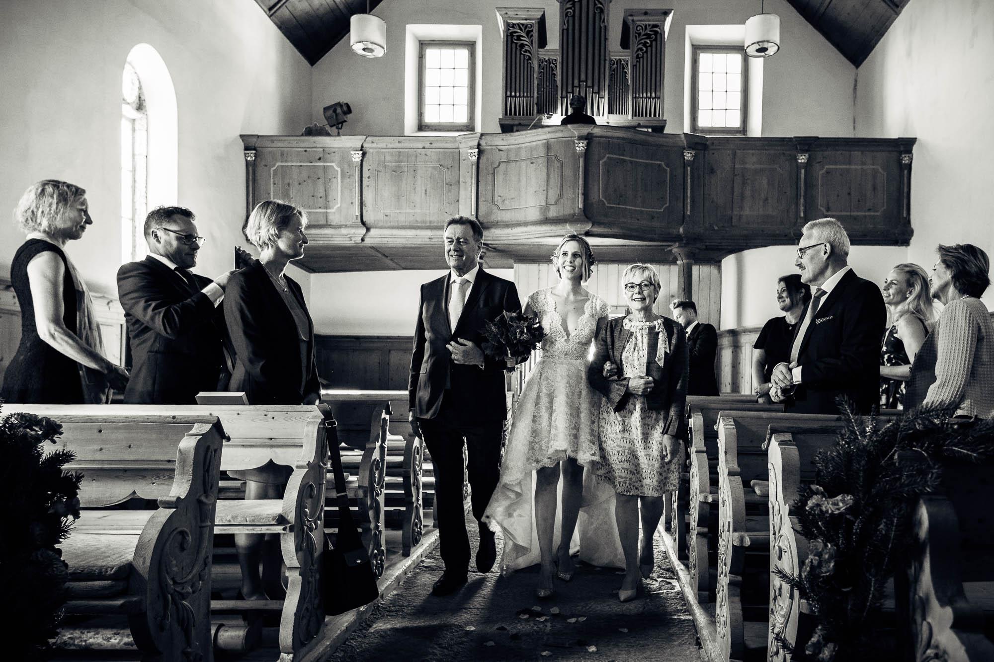 Braut wird von den Eltern in der Kirche zum Altar gebracht
