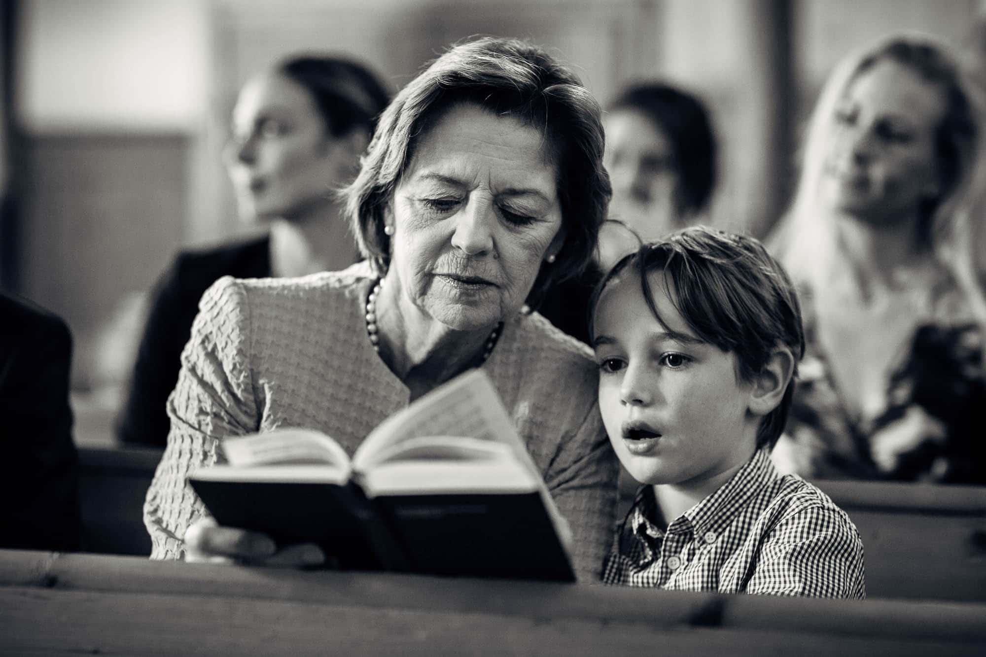 Zwei Gäste sehen in Gesangsbuch und staunen