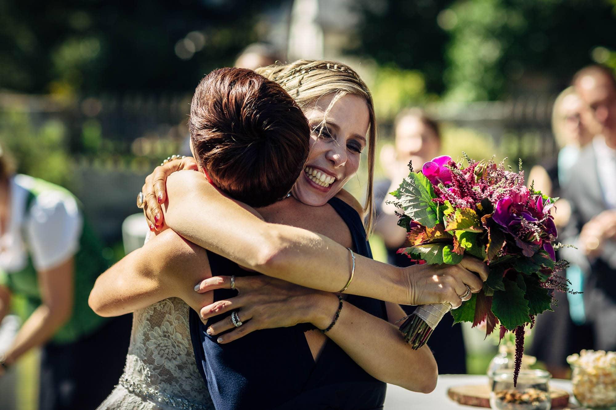 Braut umarmt Gast mit Brautstrauss