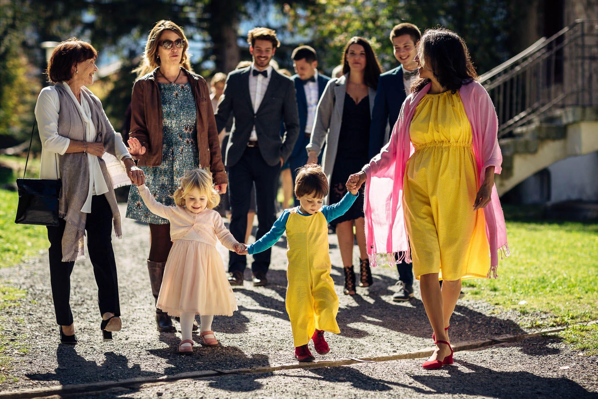 Gäste mit Kindern an der Hand gehen zur Trauung