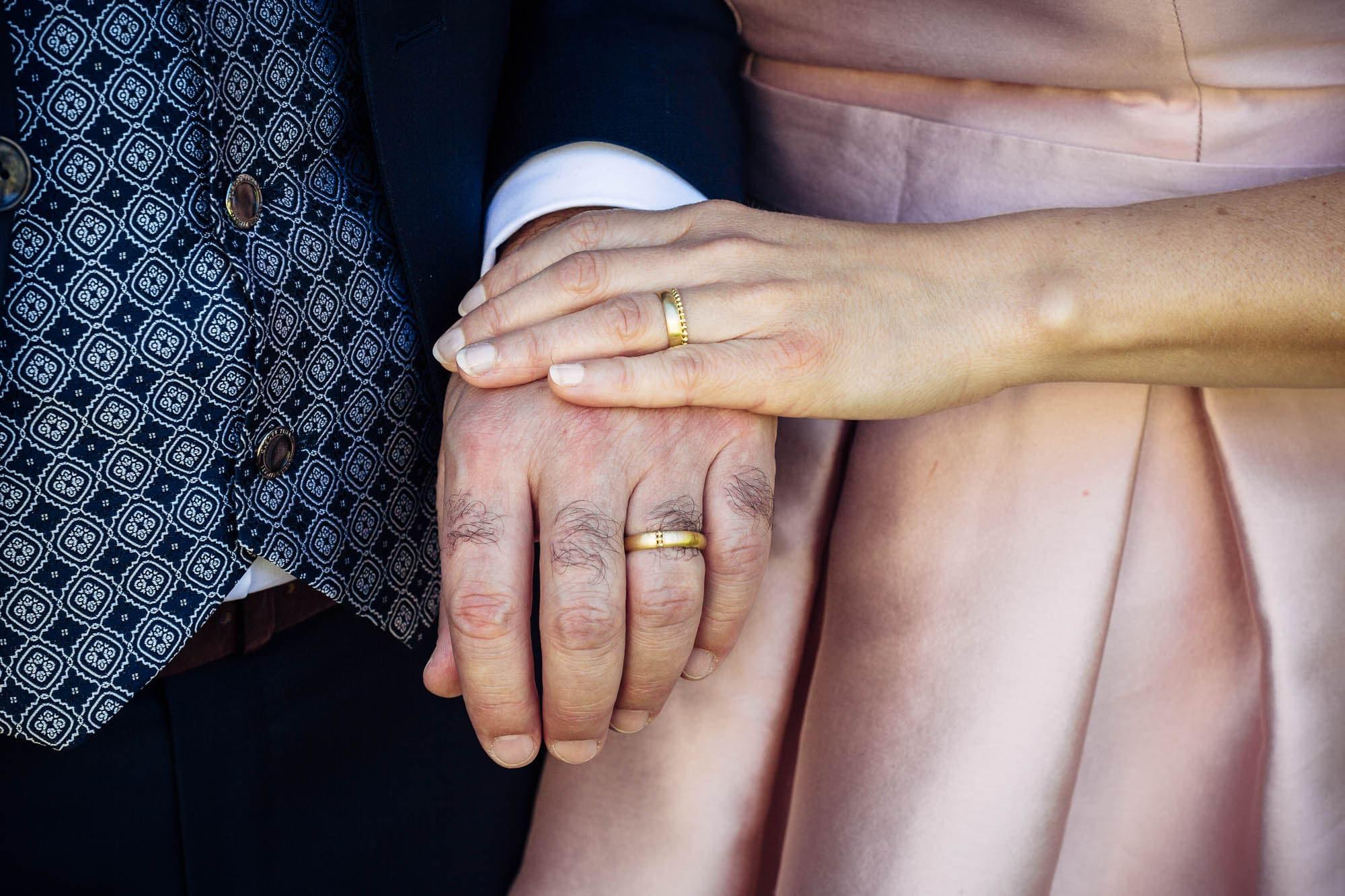 Hände von Braut und Bräutigam mit Ehering