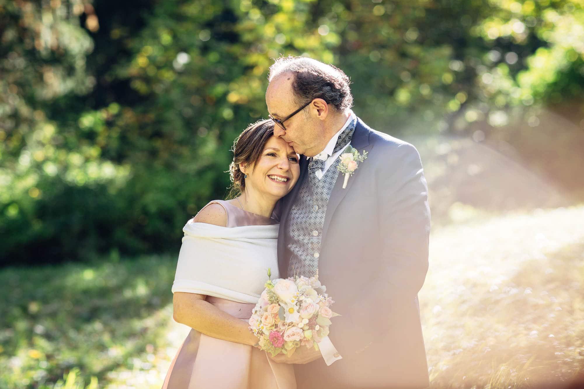 Beschützender Kuss auf Stirn der Braut