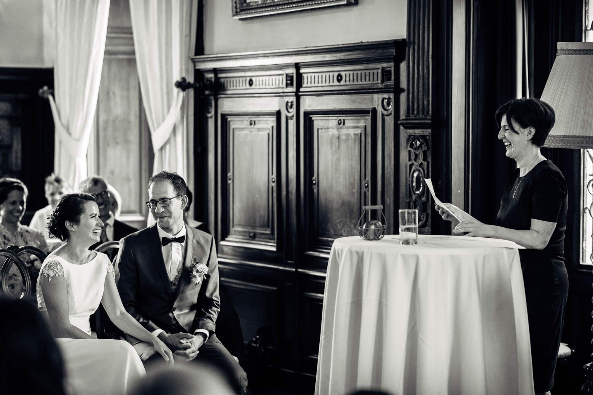 Brautpaar und Traurendnerin lachen während Zeremonie