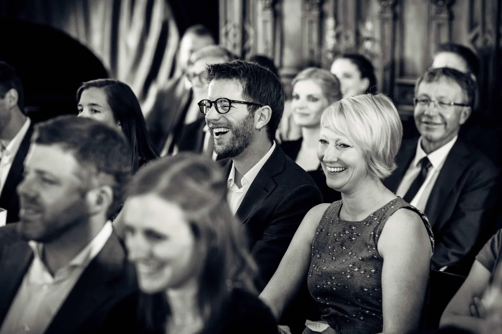 Hochzeitsgäste lachen wegen lustiger Zeremonie