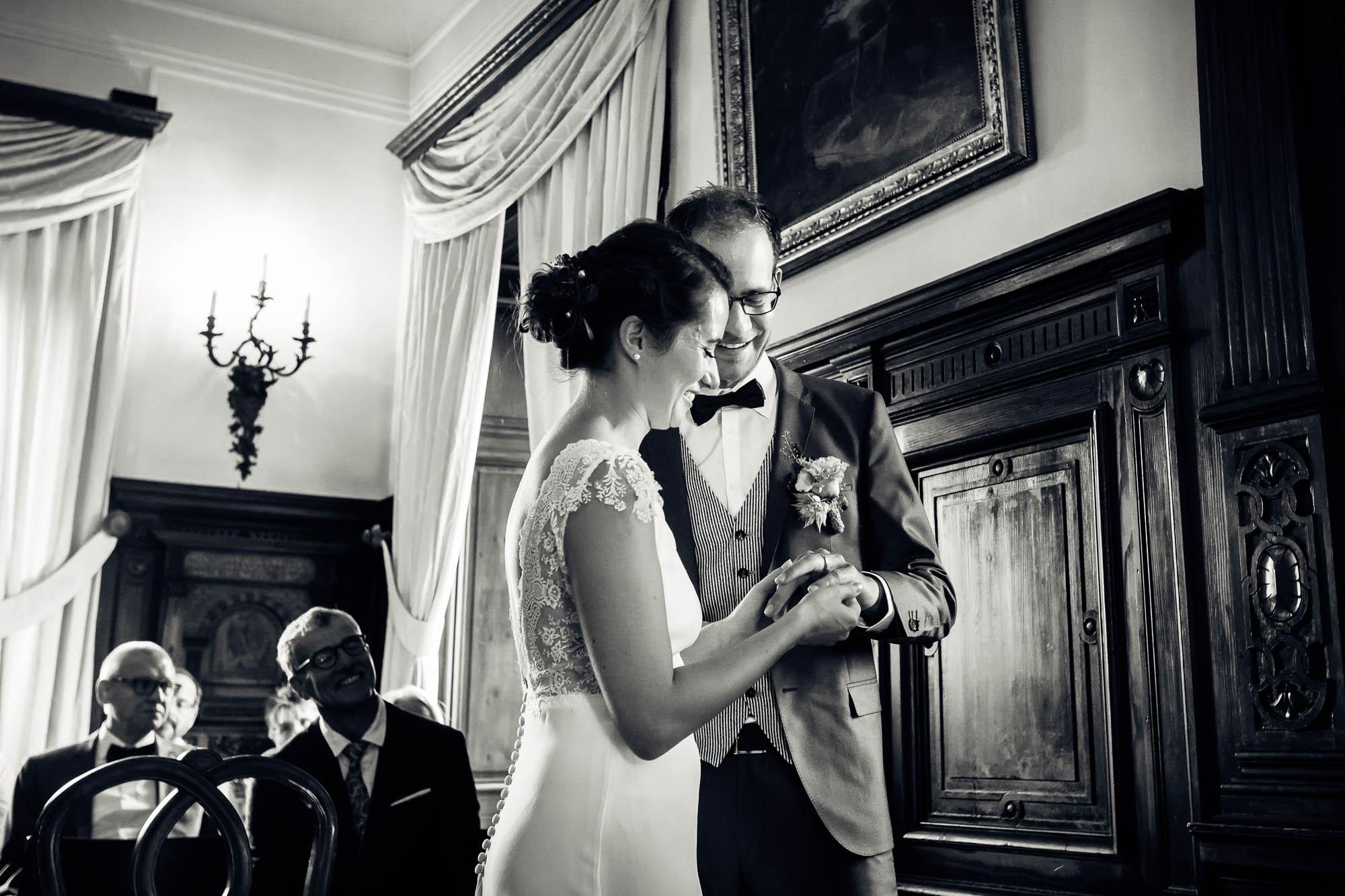 Brautpaar steckt Ring an und Brautvater schaut zu