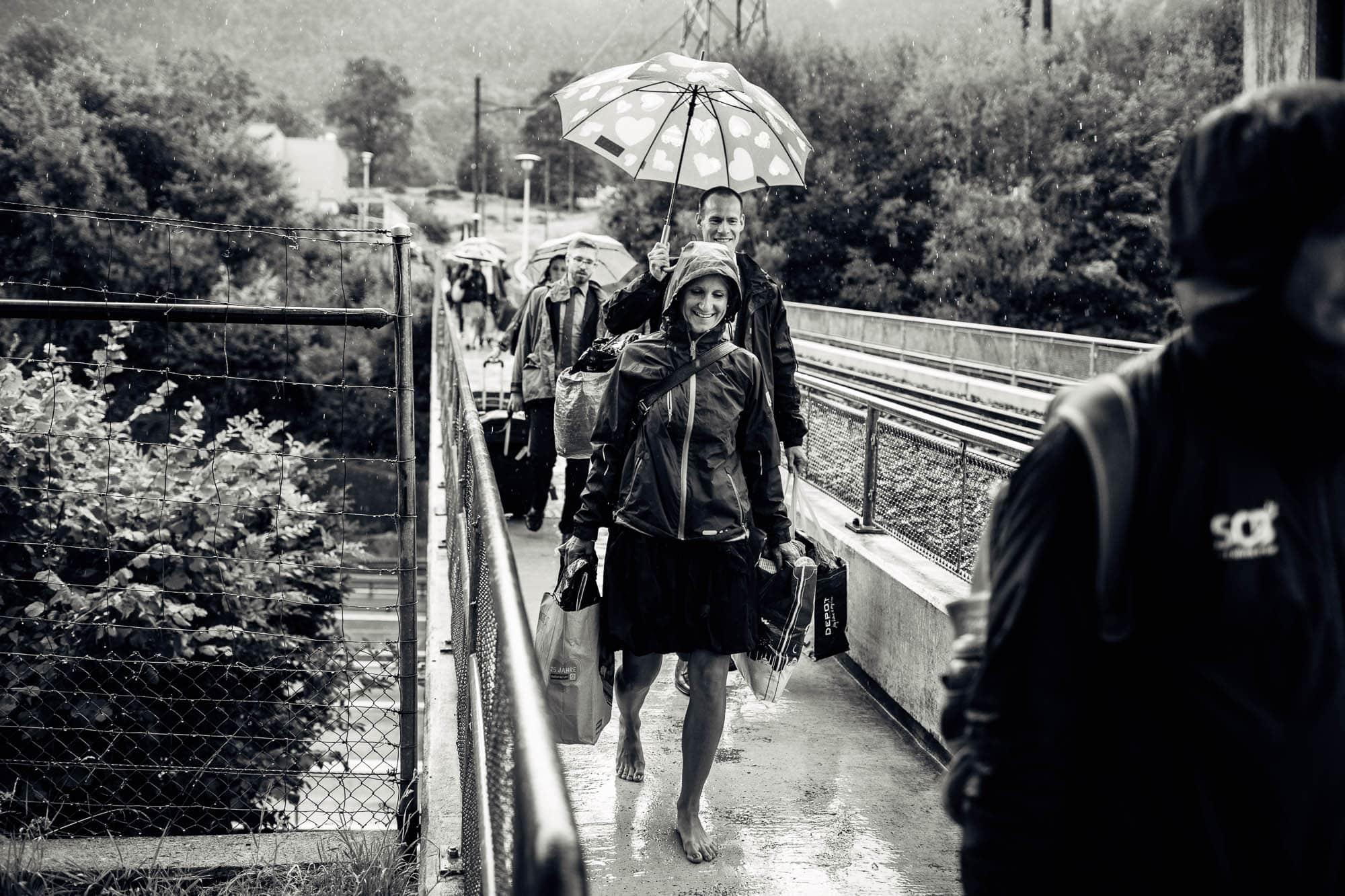 Hochzeitsgast läuft barfuss im Regen