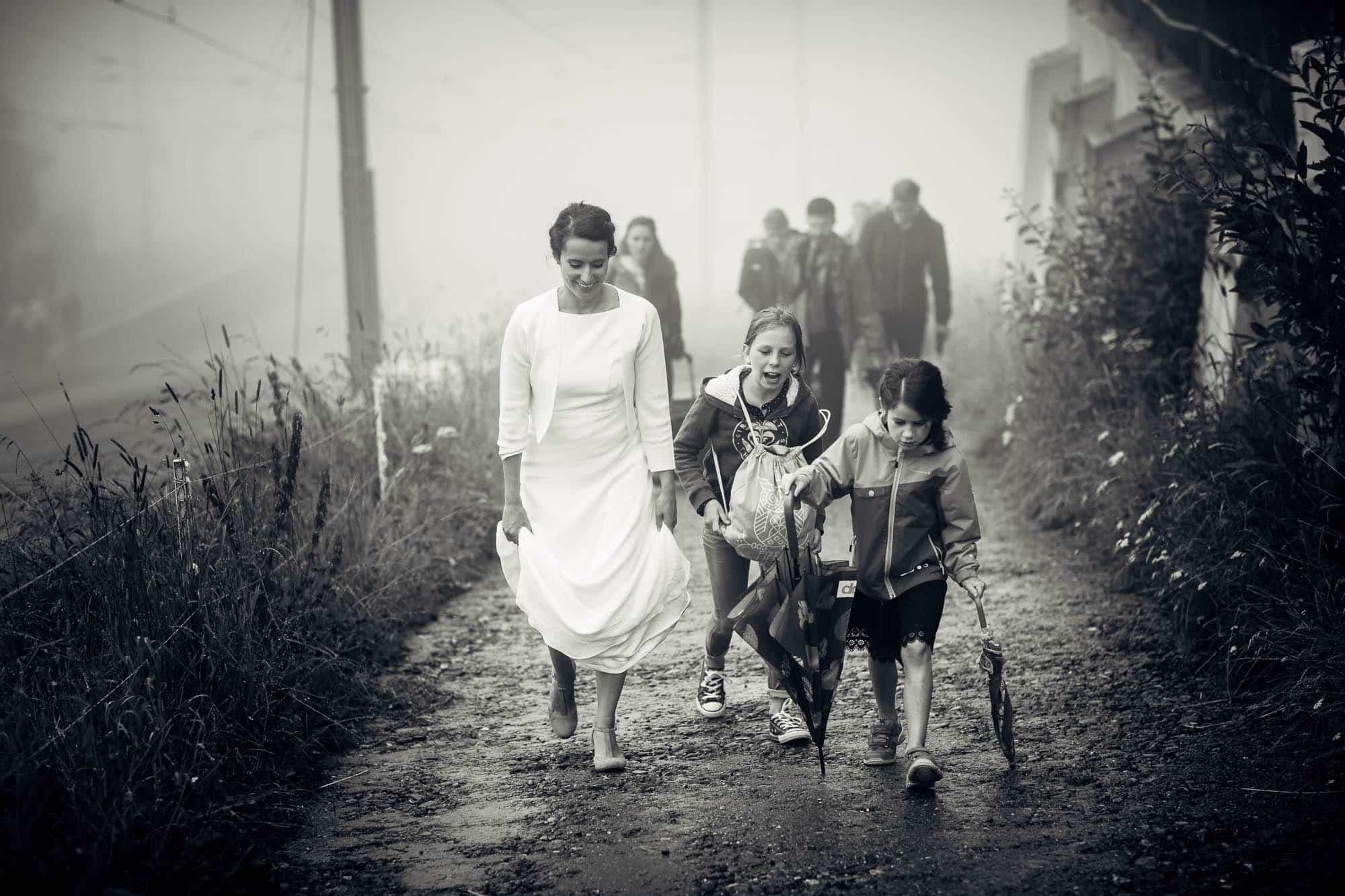 Braut und Mädchen gehen im Nebel und Regen auf einem Weg