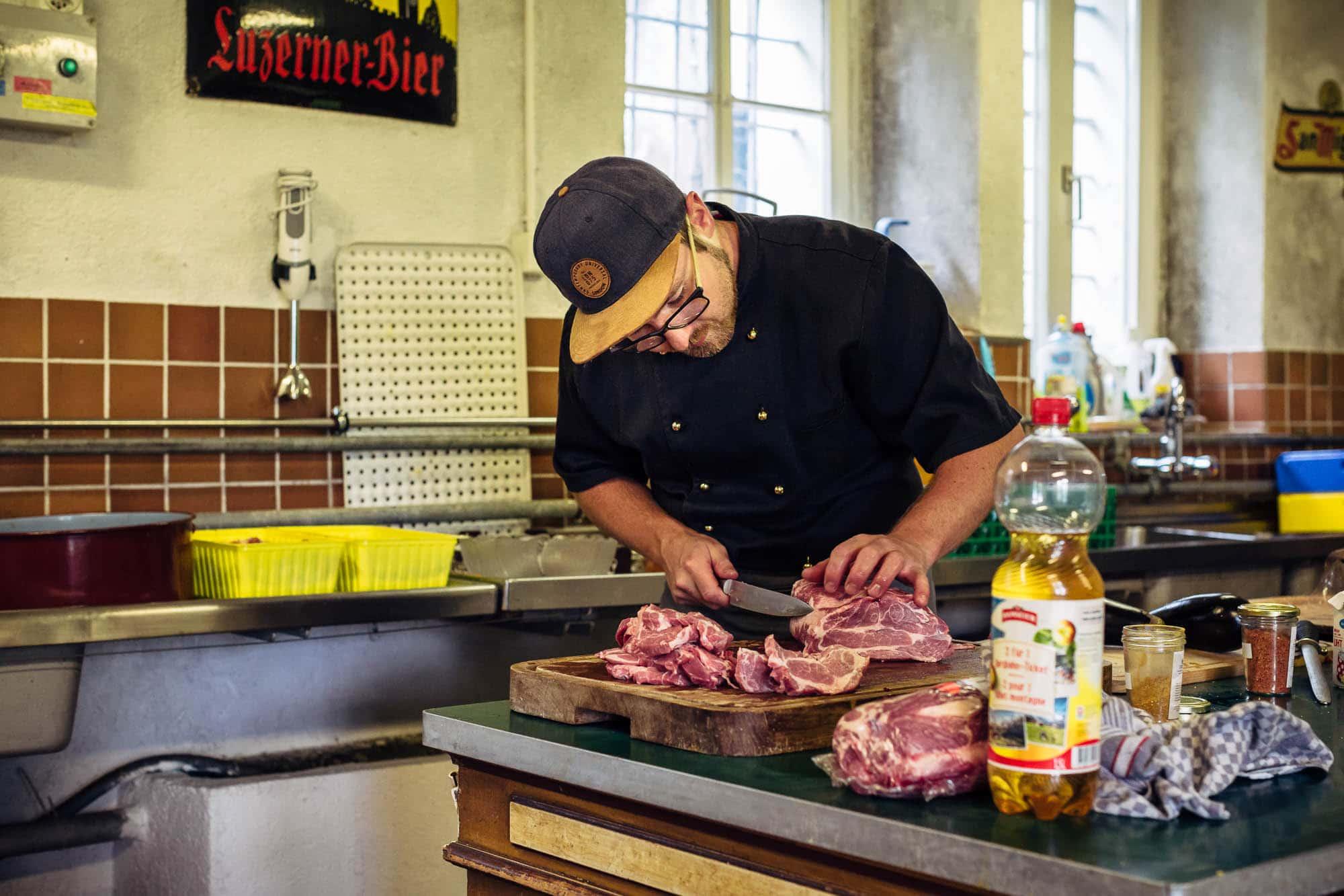 Koch schneidet Fleisch in der Küche