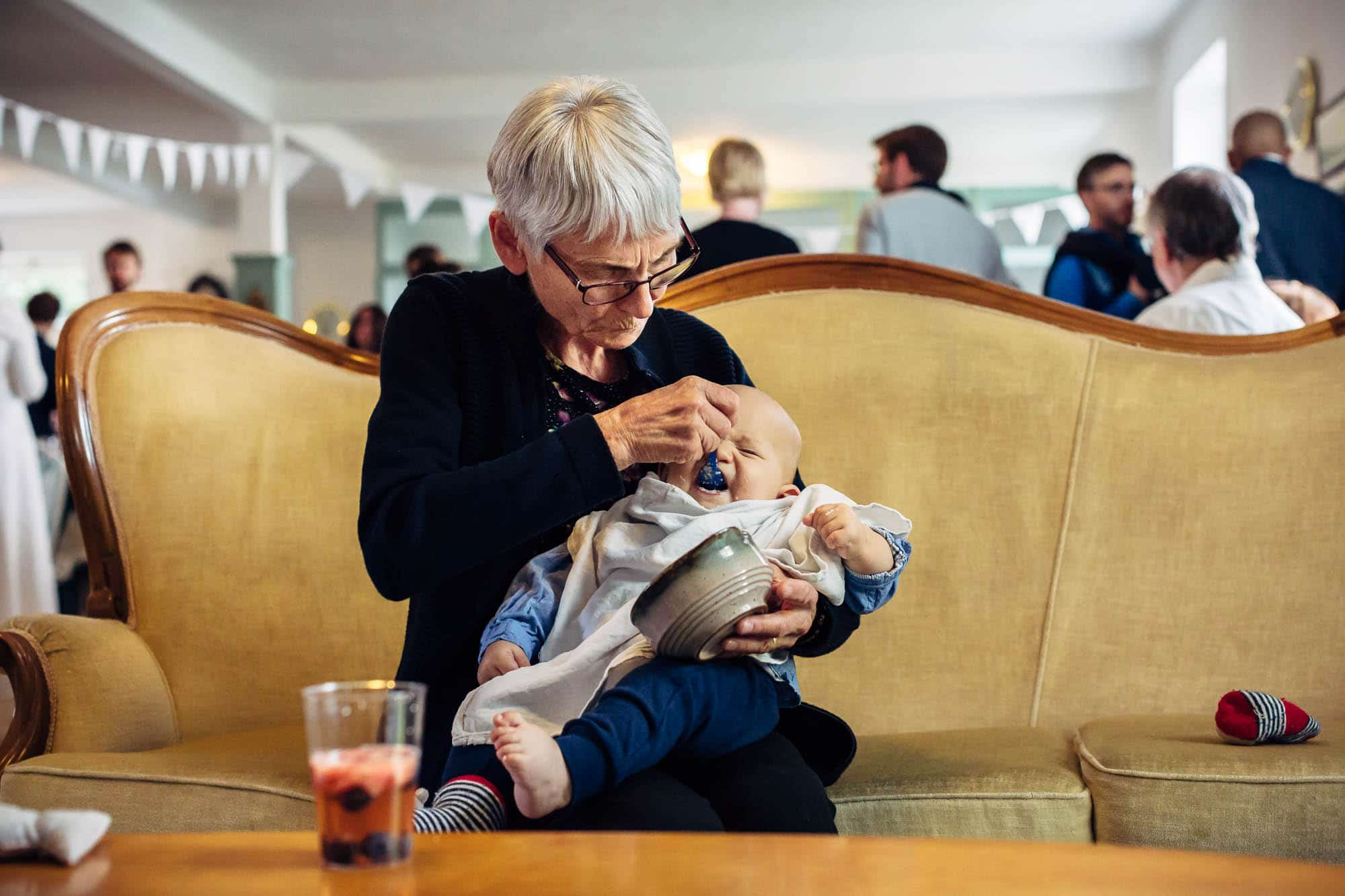 Baby wird von Oma auf Sofa gefüttert