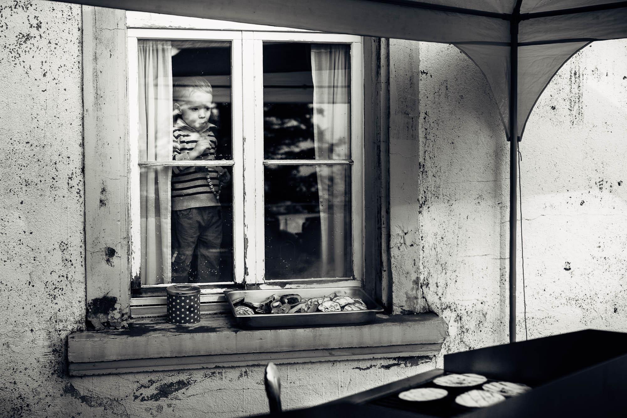 Kind schaut aus Fenster zum Grill