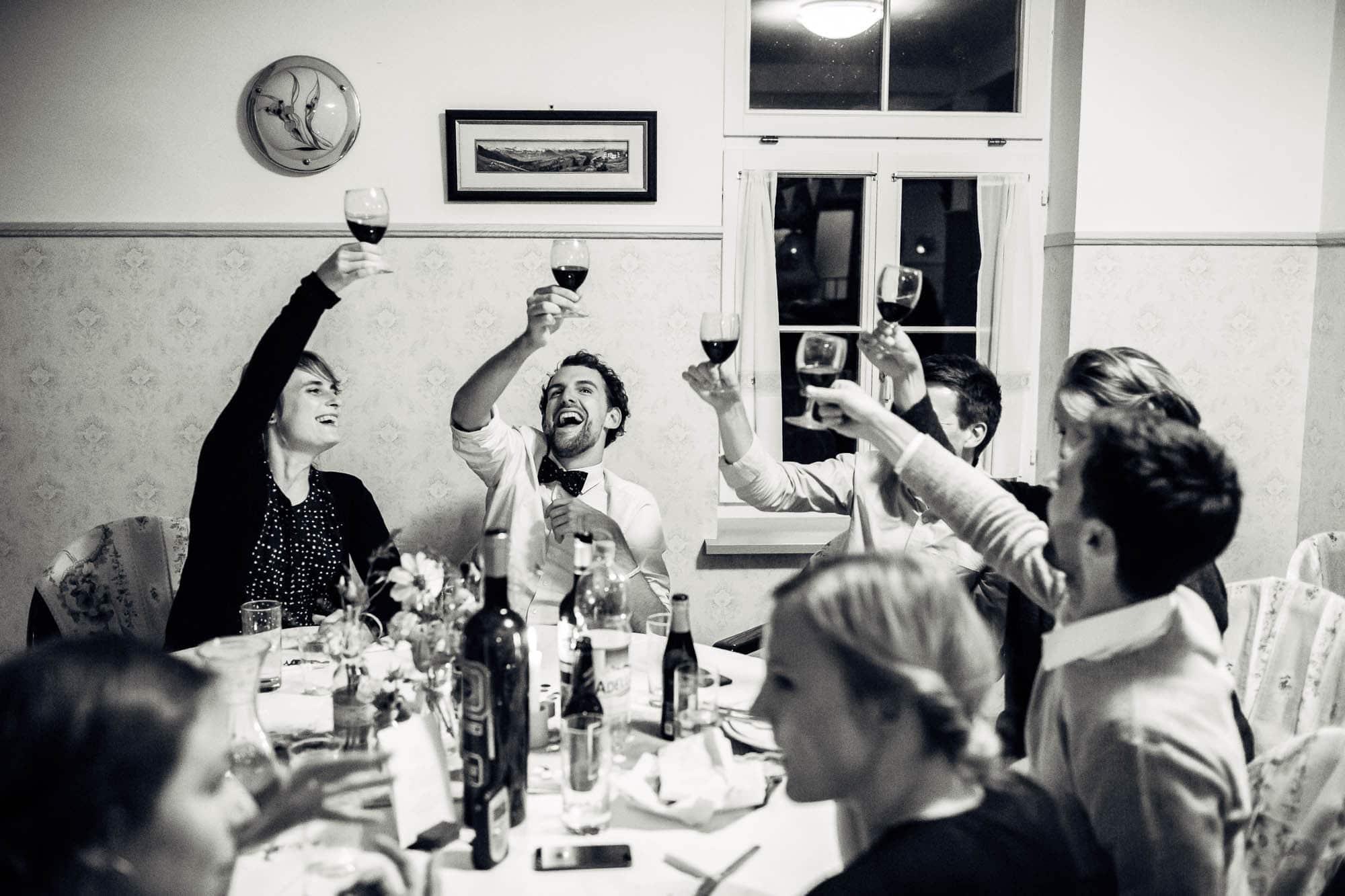Hochzeitsgäste stossen an und lachen