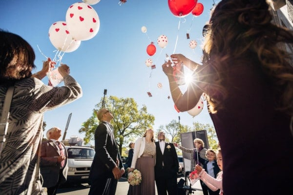 Gäste und Brautpaar lassen Ballone steigen. Sonne als Gegenlicht