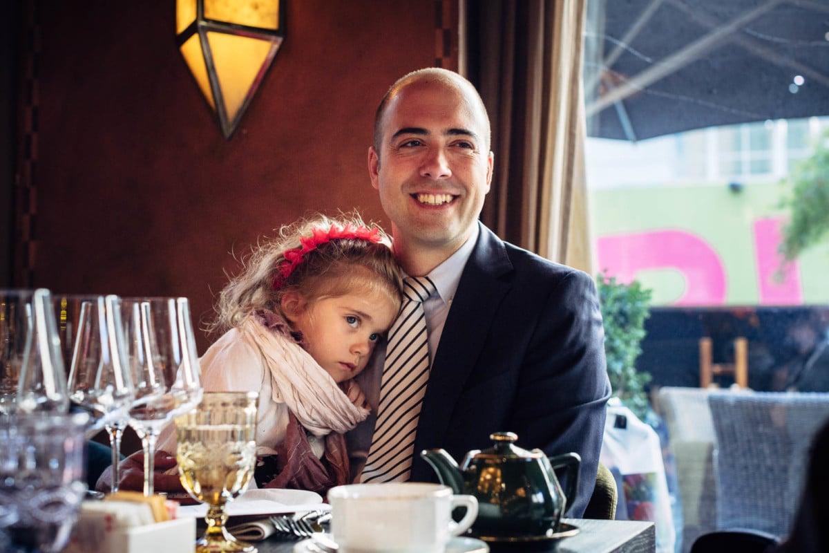Müde Tochter schmiegt sich an Brust von Vater im Restaurant