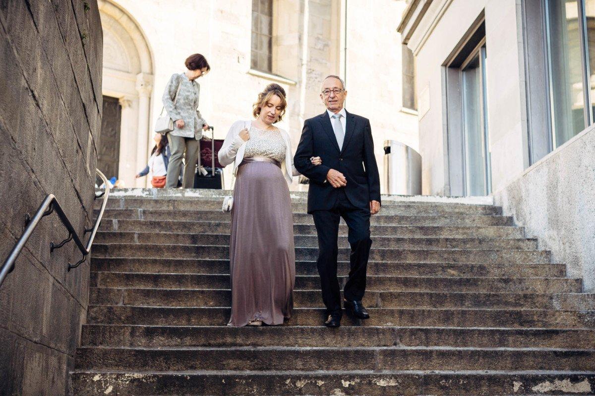 Braut wird vom Vater die Treppe hinunter geführt