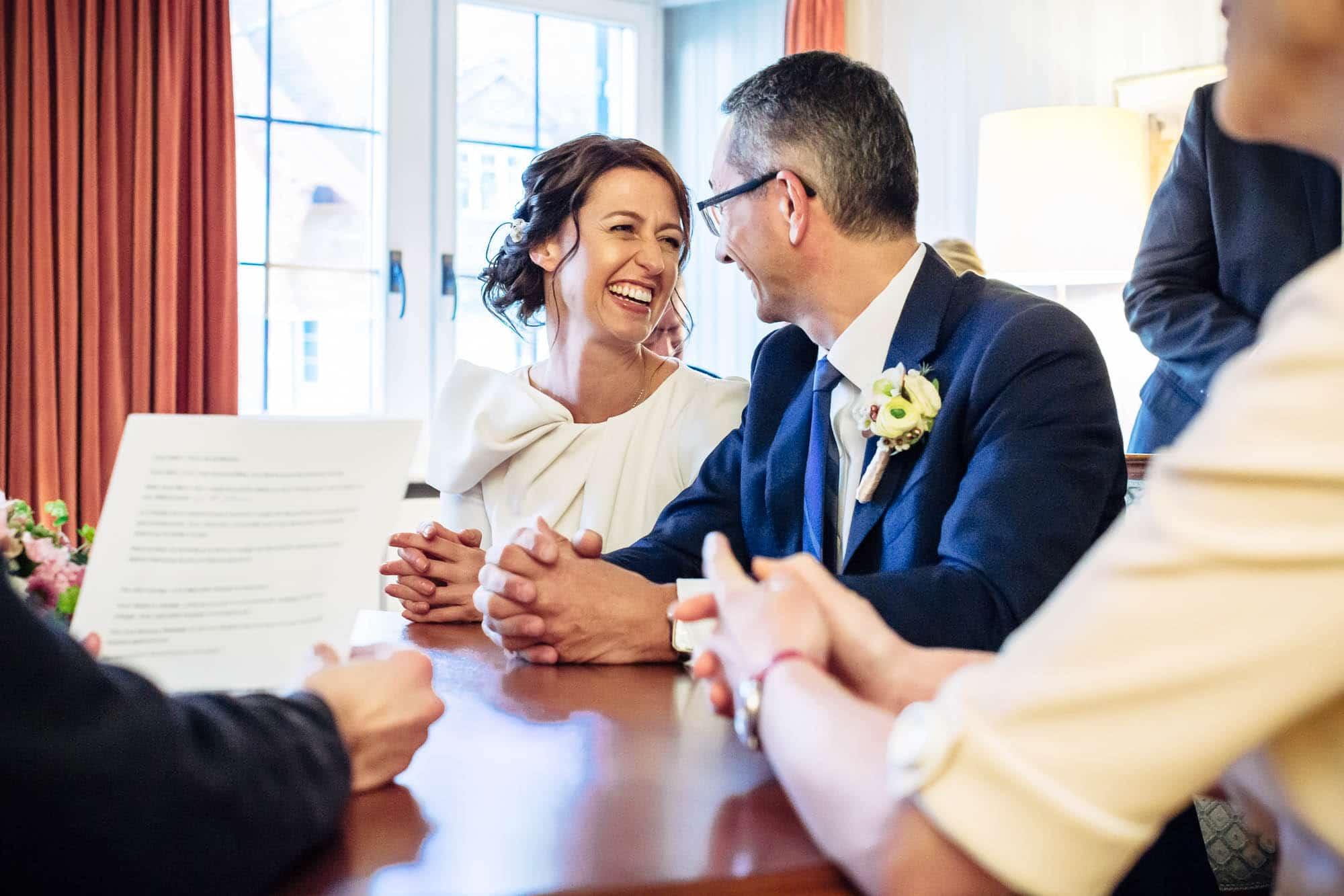Brautpaar lacht herzhaft währen Zivilhochzeit