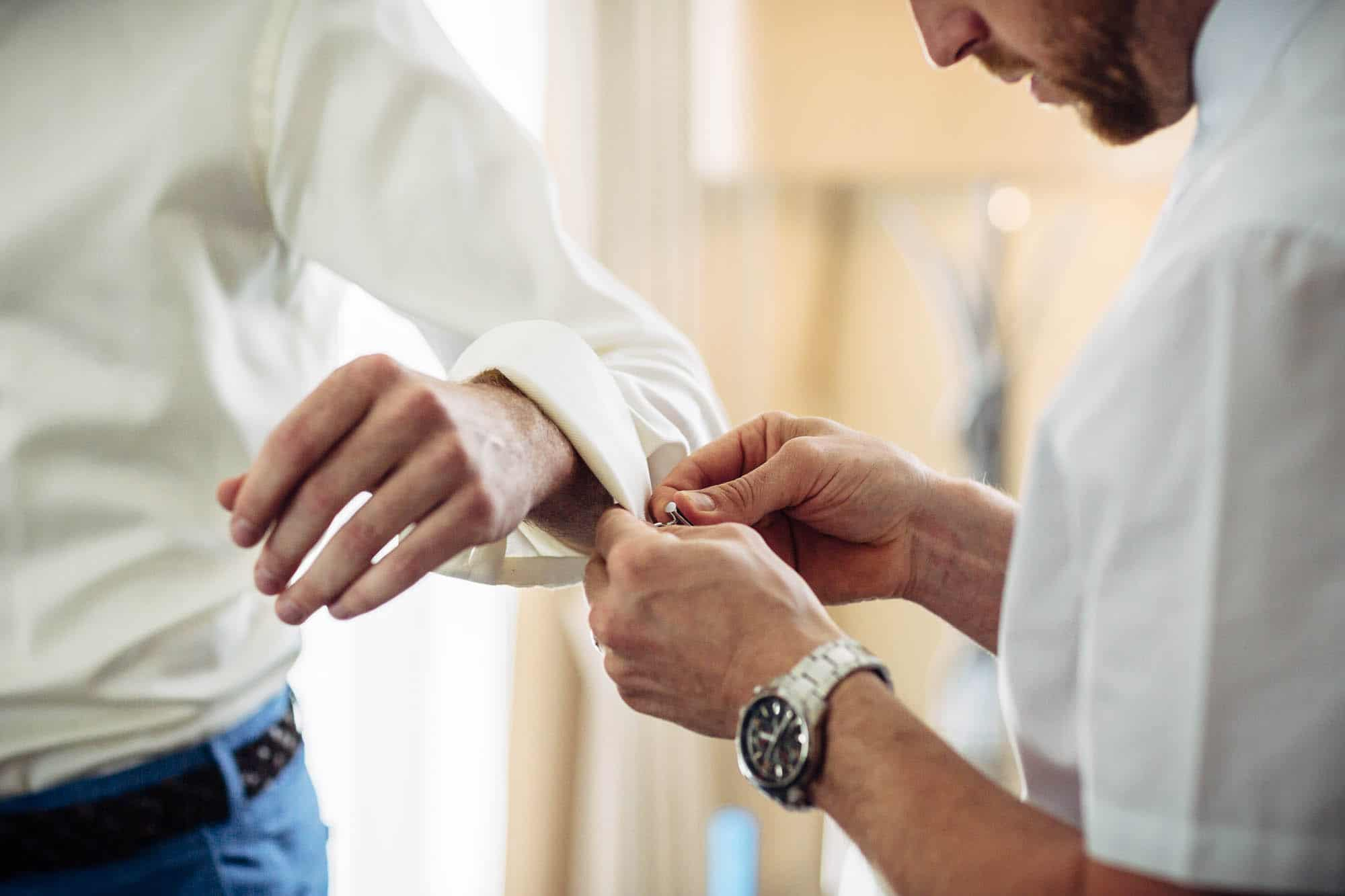 Trauzeuge hilft dem Bräutigam beim Anziehen der Manschettenknöpfe
