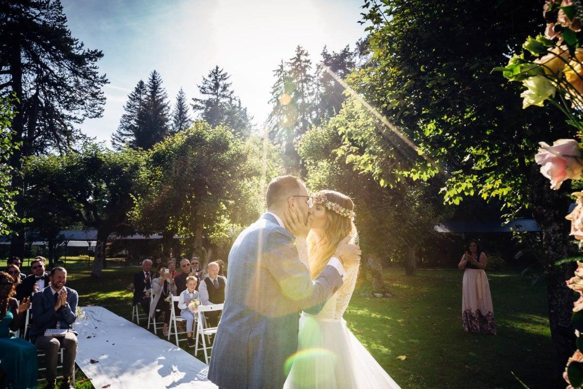 Brautpaar küsst sich im Sonnenschein nach Ringtausch