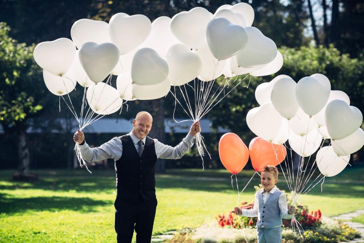 Vater und Sohn halten viele Luftballone