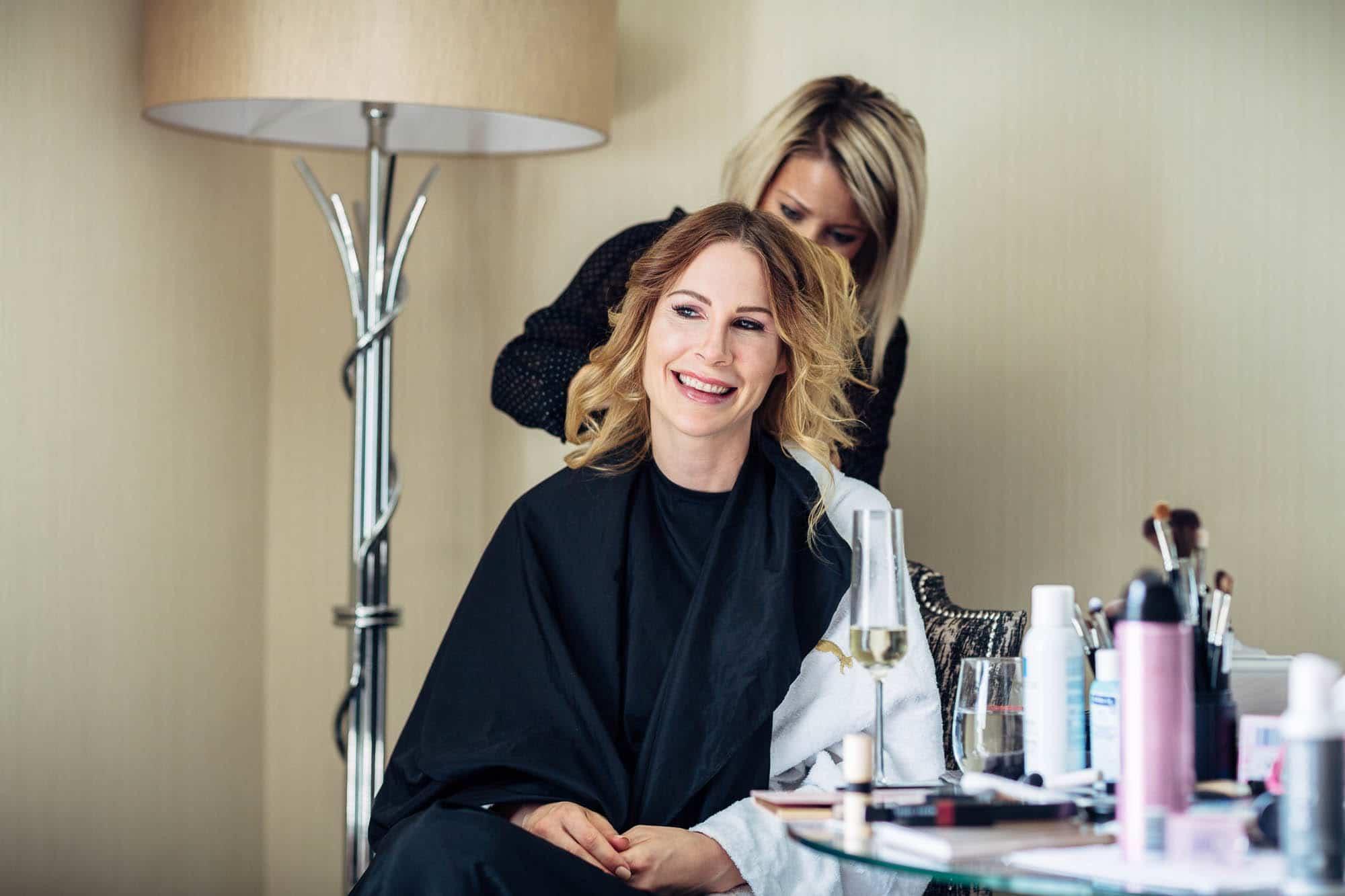 Braut lacht beim Hairstyling