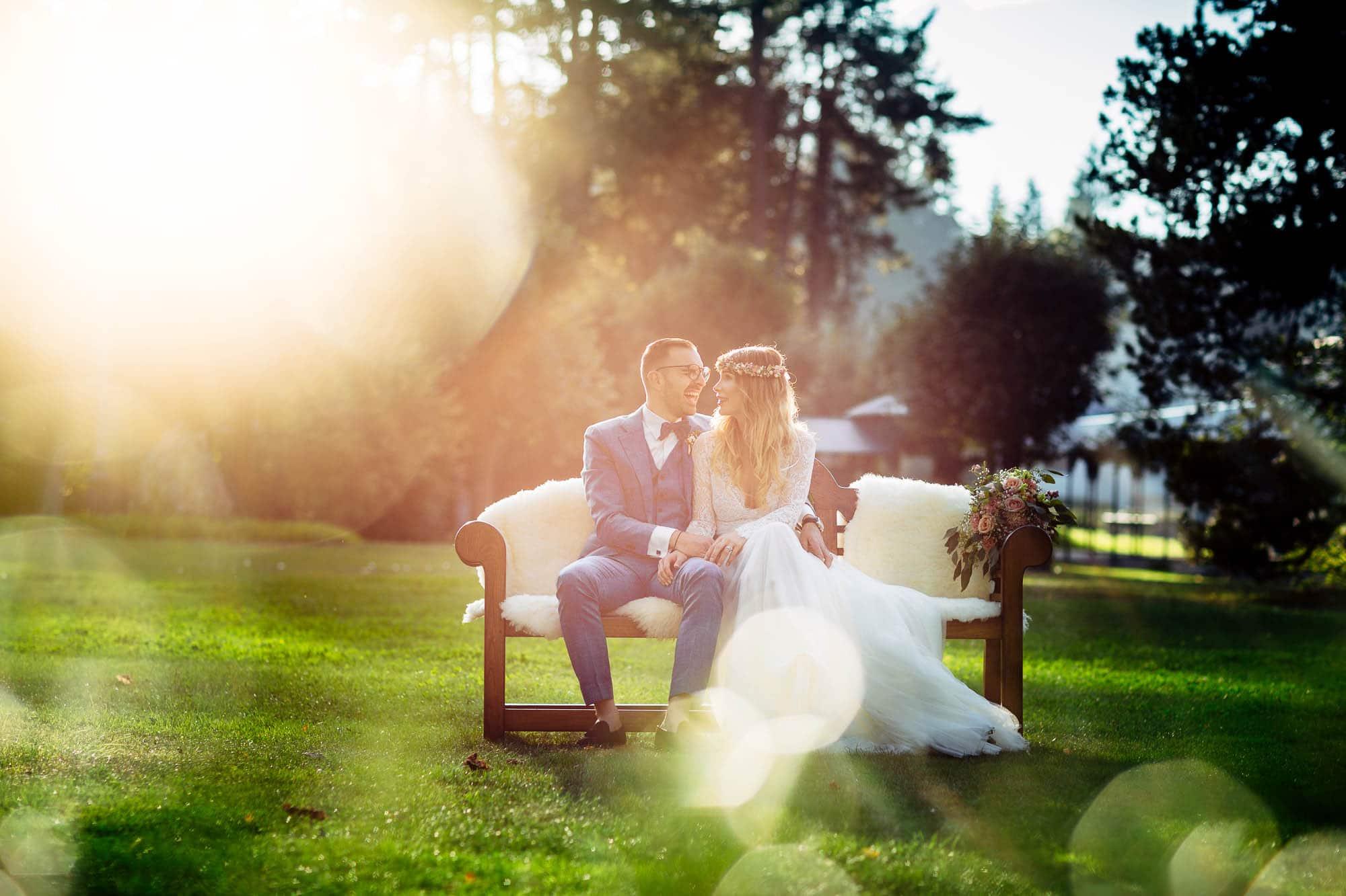 Brautpaar auf Bank an Hochzeit im Waldhaus Flims