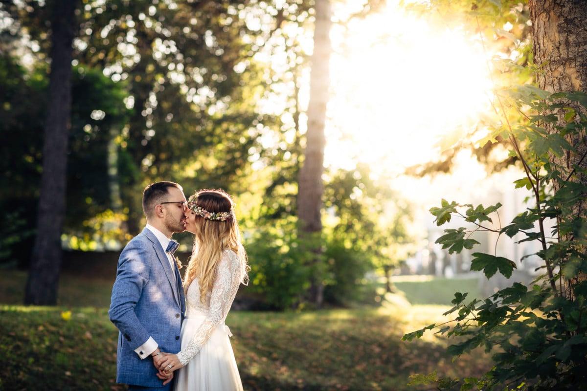 Brautpaar küsst sich im Sonnenschein. Hochzeitsfotograf Flims