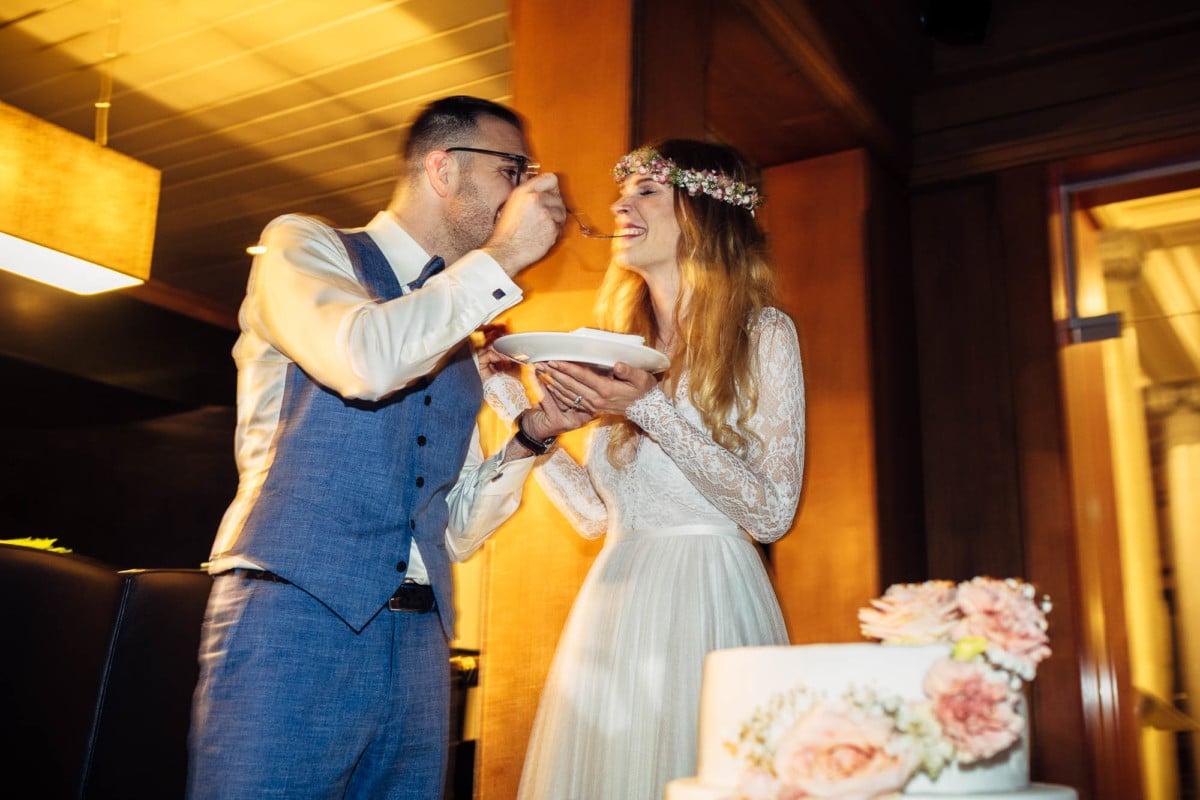 Brautpaar füttert sich gegenseitig mit Hochzeitstorte