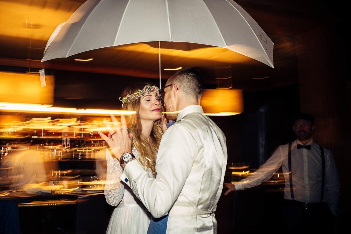 Brautpaar tanzt unter Regenschirm in einer Bar