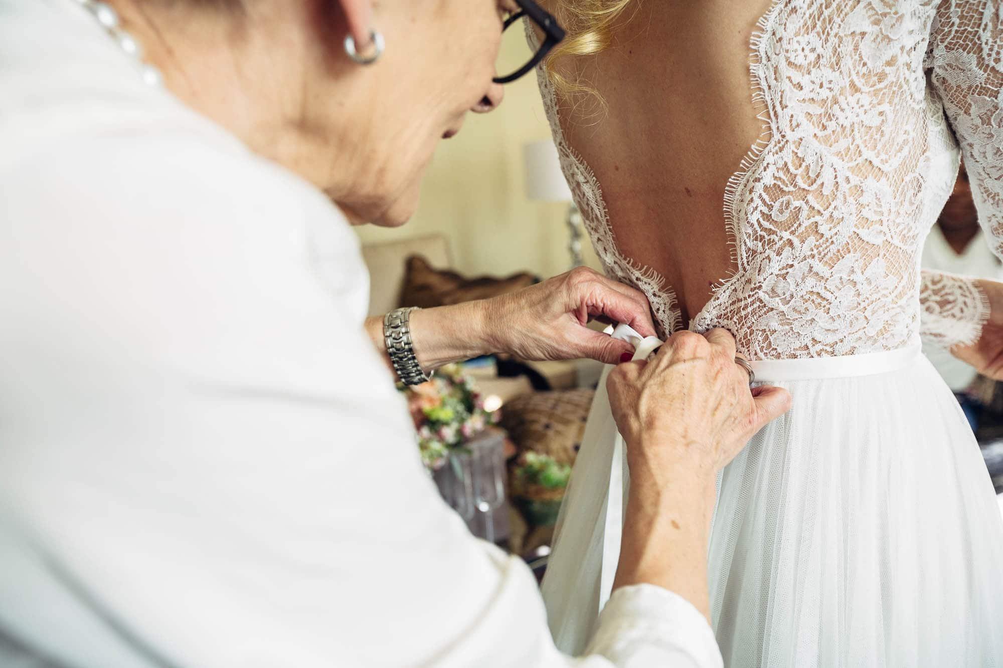 Der Braut wird das Kleid gebunden