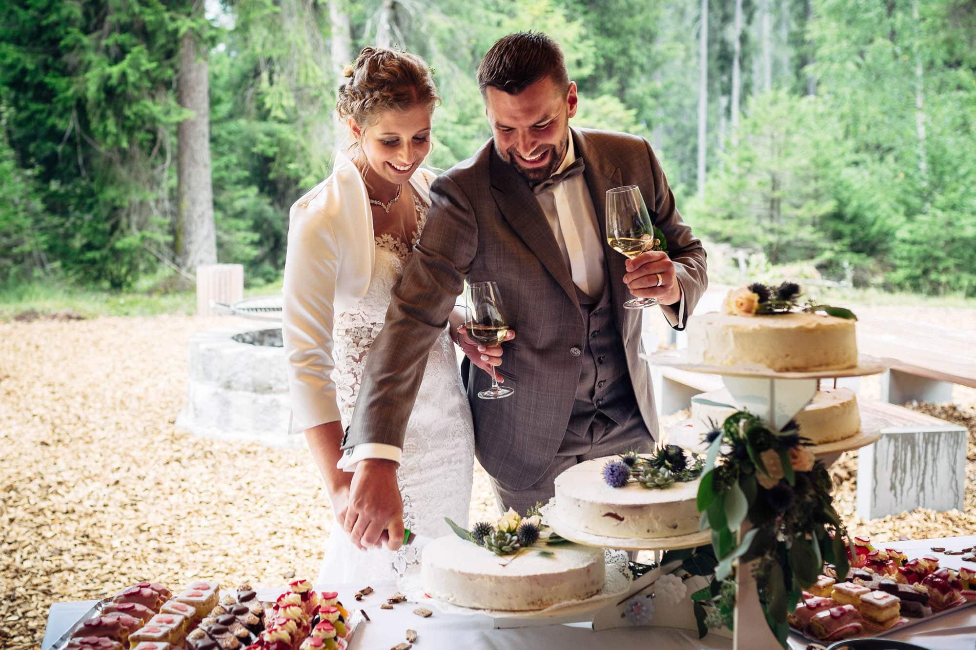 Brautpaar schneidet Hochzeitstorte in der Waldhütte Salums an