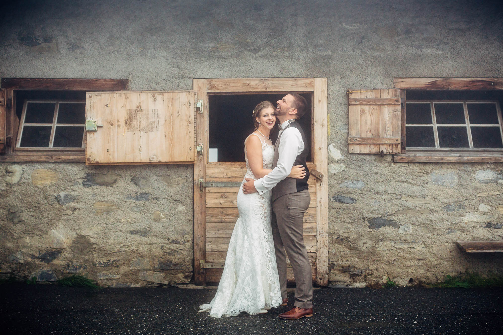 Hochzeitspaar im Nebel stehend vor Alpgebäude