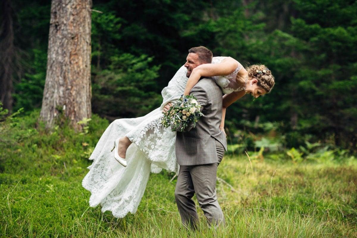 Bräutigam nimmt Braut über auf die Schulter